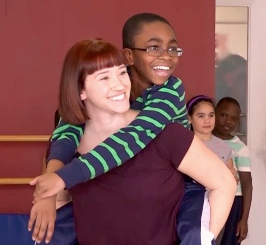 Female dancer carries young boy on her back in rehearsal. Both are laughing.