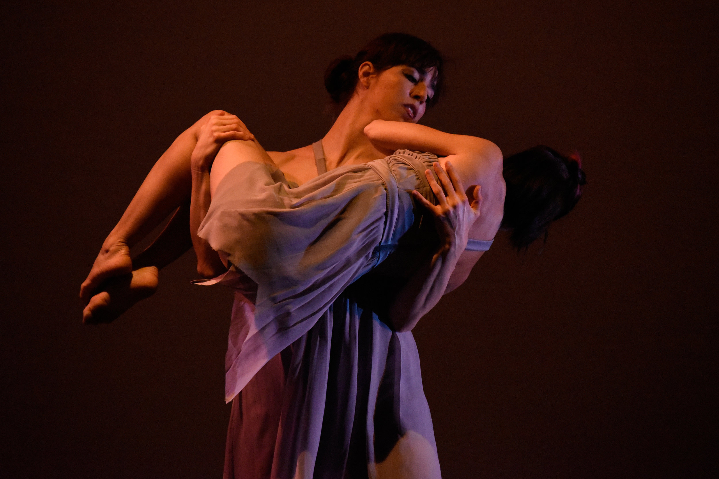 Kelly Vaghenas and Lisa Clementi. (Photo Russell Haydn).  (A female dancers carries and holds another woman who is folded into a fetal position around the first woman's chest and arms).
