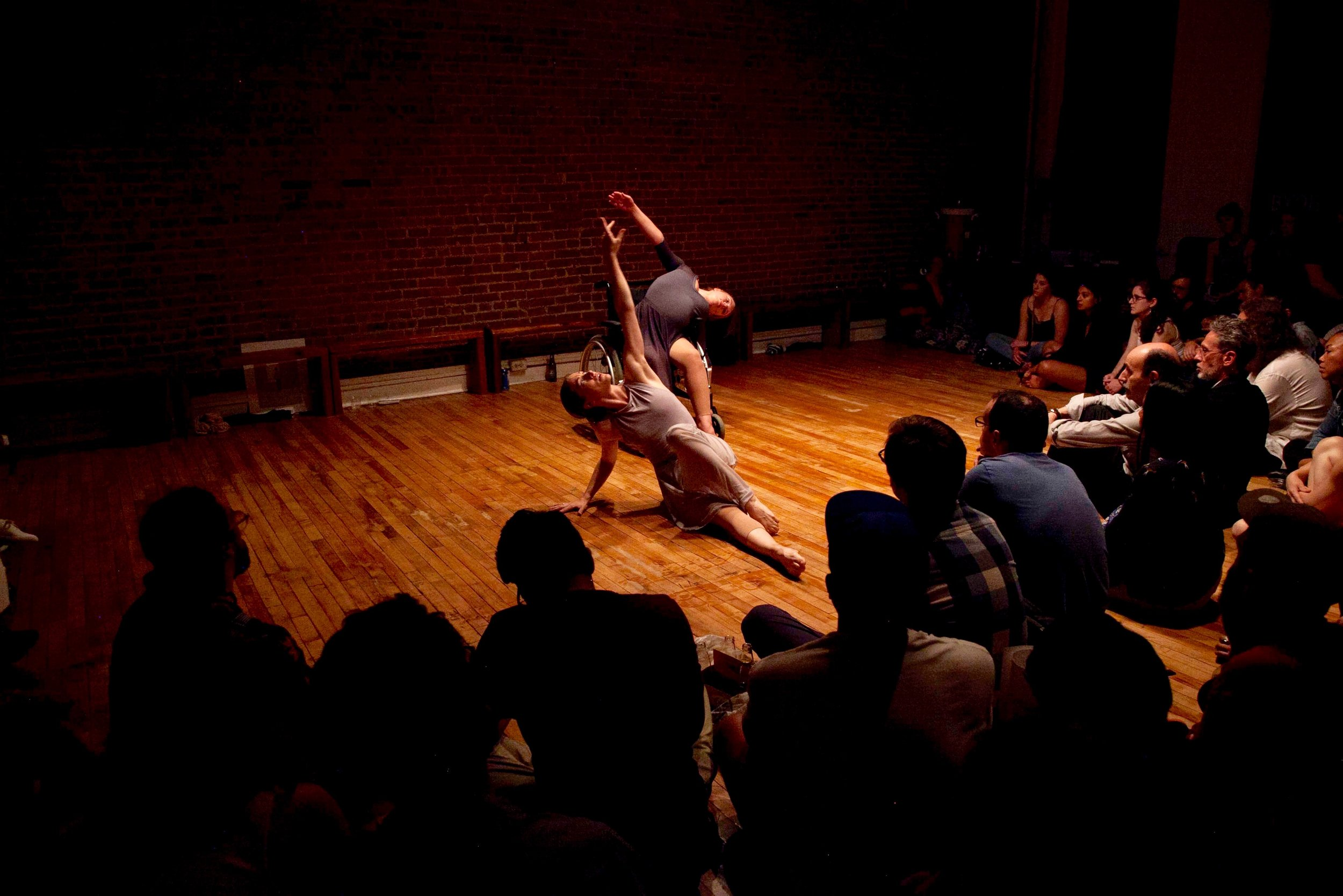 Madeline Charles and Madison Ferris. (Photo: Kyle Netzeband).  (Audience seated on floor around two female dancers in grey dresses reaching up high. One woman is seated on the floor, the other in a wheelchair).