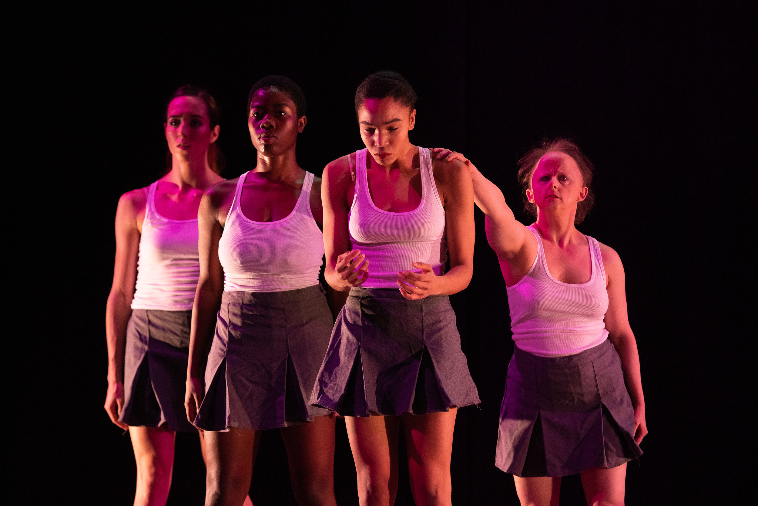 Sshhh:   Four women in grey school uniform skirts and white tank tops form a clump while one dancer reaches out to one of the women who is contracting her shoulders with her hands held in fists and looking down. Photo: Steven Pisano