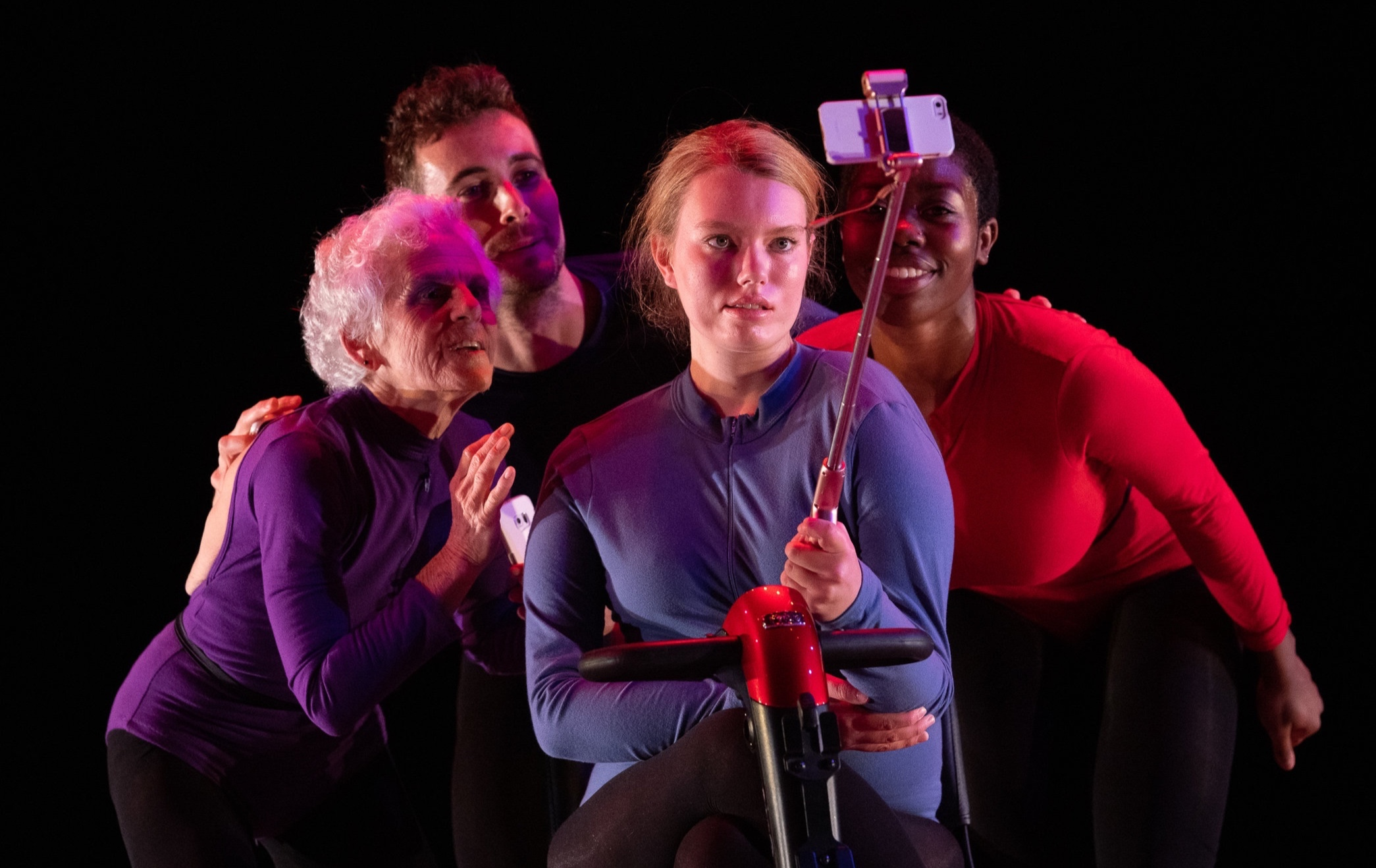 Phantom Limb:   Four dancers in red, purple and blue tops are grouped together posing for a phone on a selfie stick. Photo: Steven Pisano