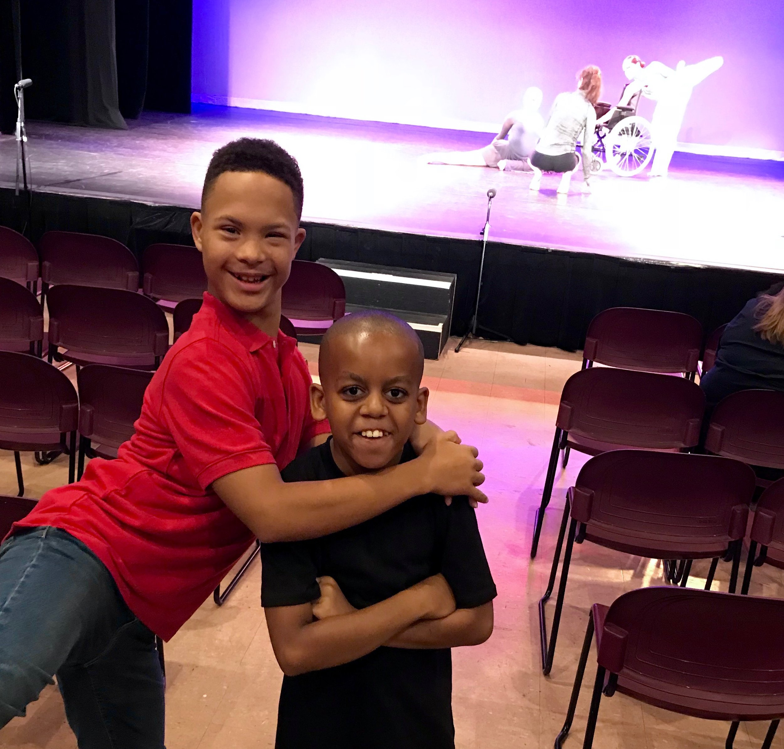 Apprentice Malik and student-dancer Kamran hug and smile at the camera at the O photoshoot. In the background are Melissa and two dancers getting ready for some photos.