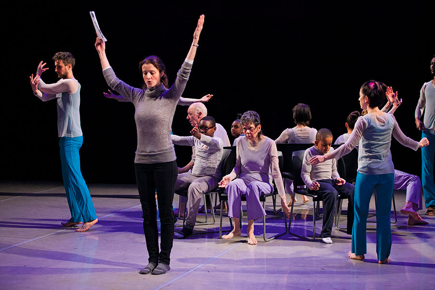 Melissa goes over choreography with the intergenerational dancers from a piece titled  Only Connect.  8 of the 12 dancers are seated on a circle of chairs.