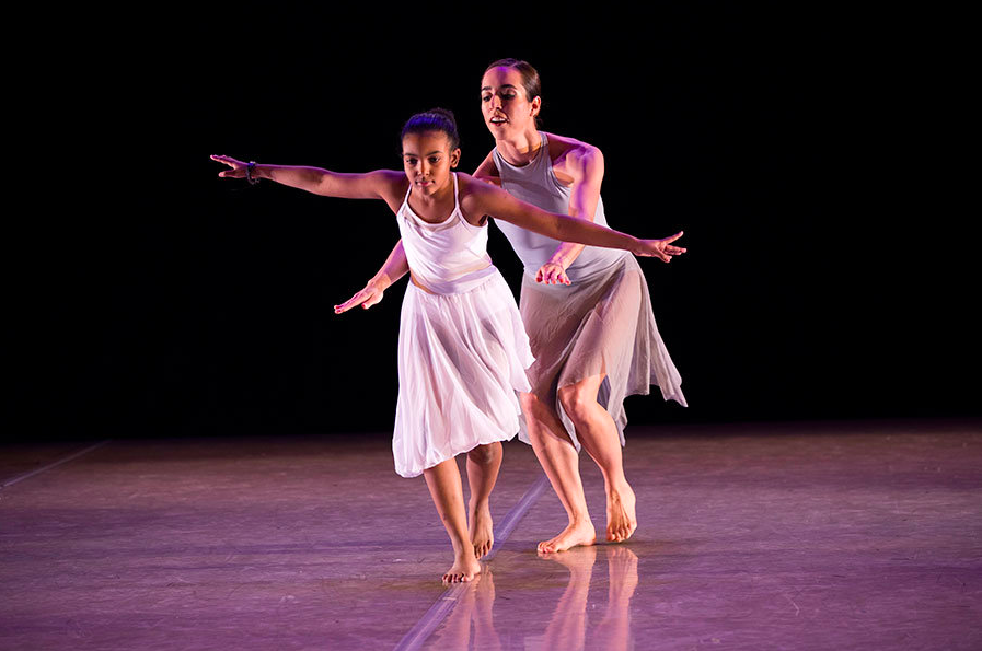 Dancer Kelly Vaghenas and student-dancer Emily perform and move as though on a balance beam.