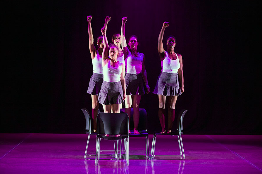 Five women stand on chairs with one arm up and fists raised.