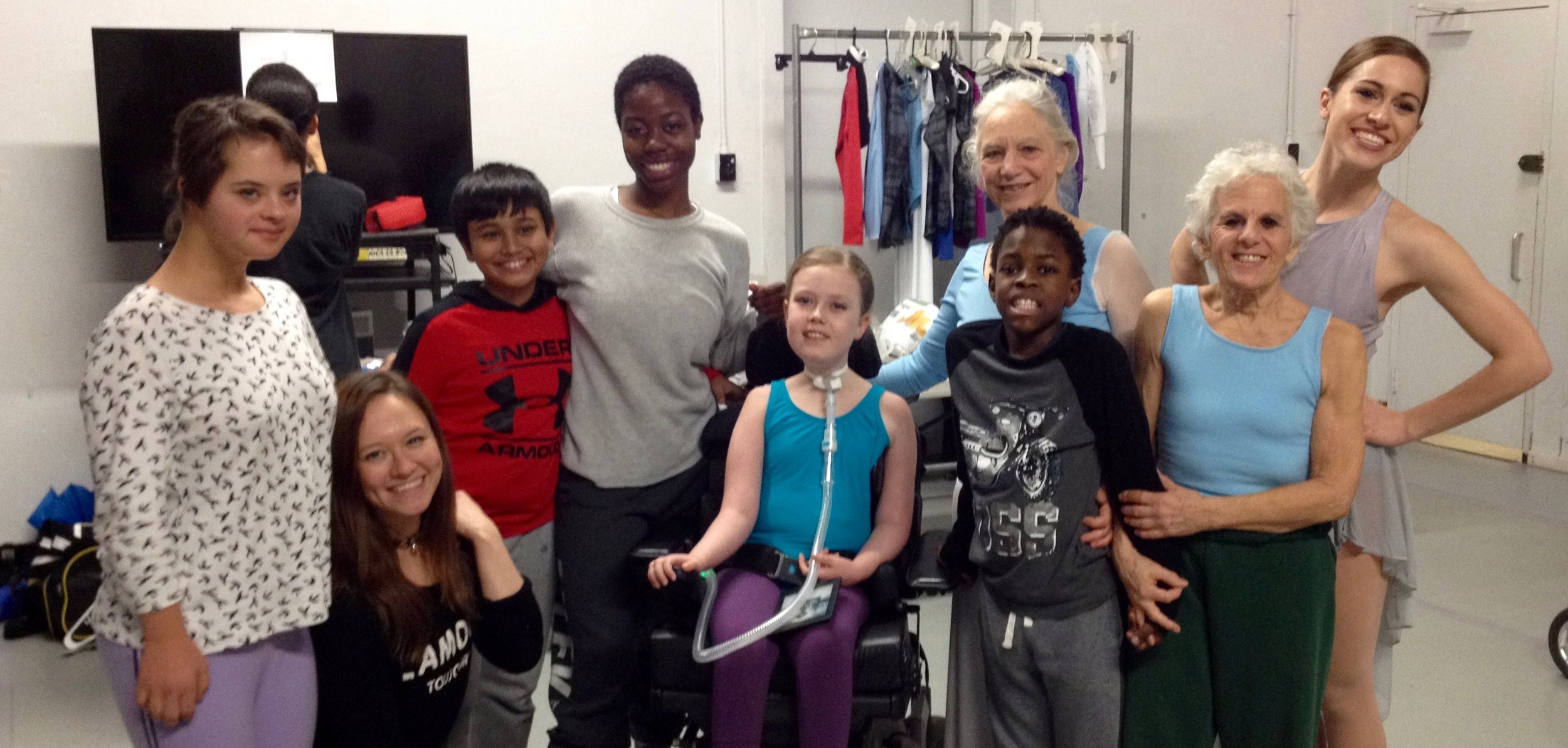 Four dancers, the Student-Coordinator, and four student-dancers posing and smiling for the camera in the dressing room.