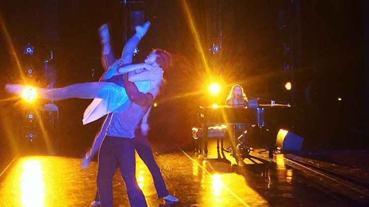 Female dancer being lifted with legs extended out with Misty at a baby grand piano in the background. Bright yellow lights create a sun burst effect. PHOTO: Jake Elvig