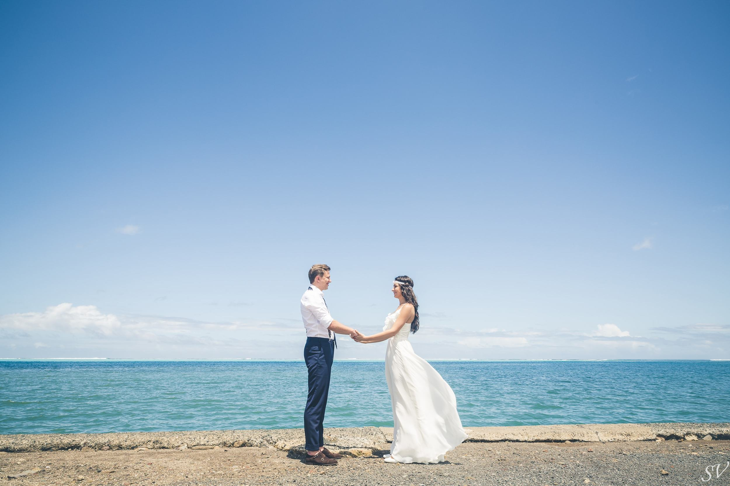 Bride and groom with the ocean for background