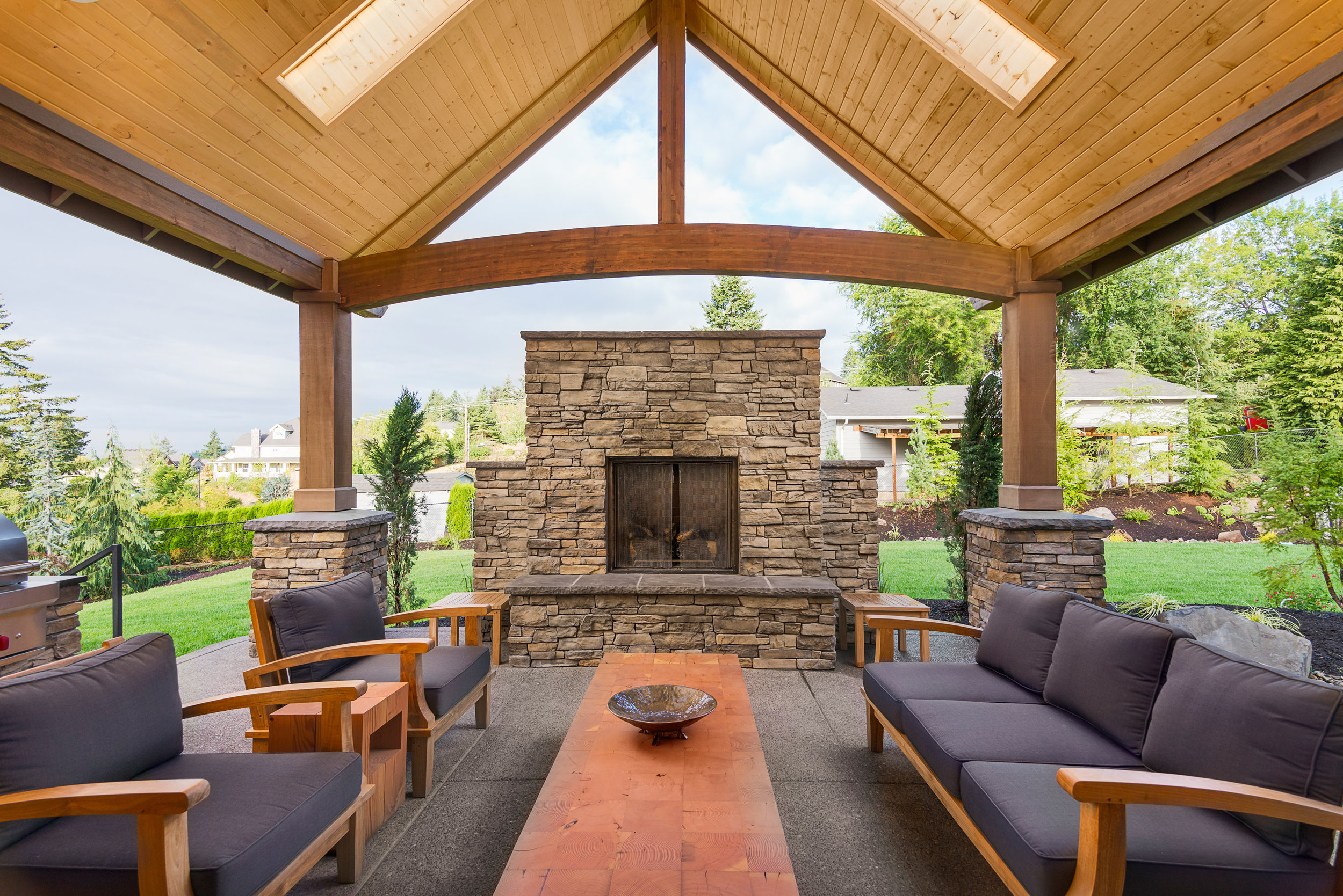 covered room outdoor pavilion fireplace patio landscape design plantings