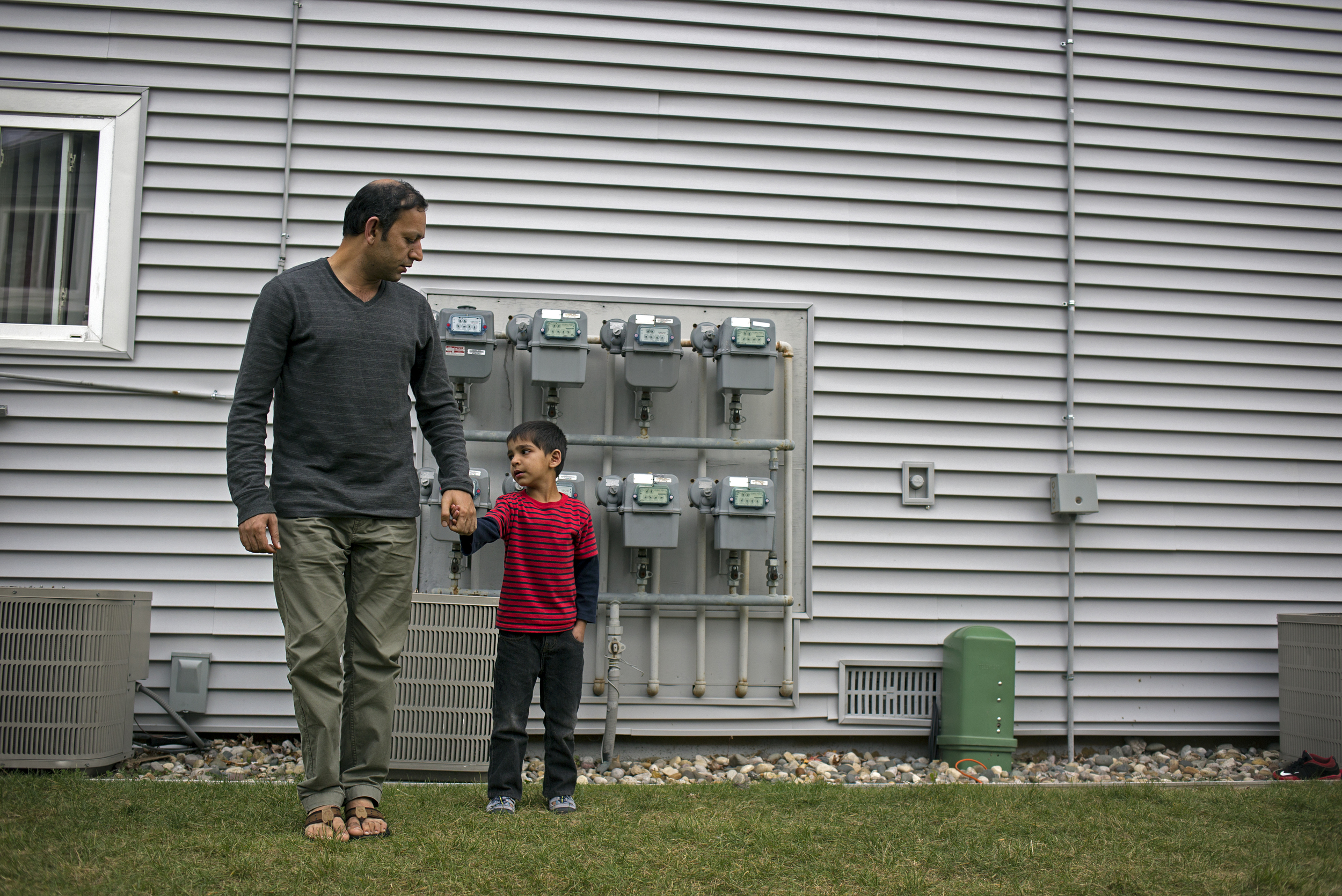 Ezatullah, 38, stands with his youngest son, Ehsanullah, 6, after he got hurt playing soccer with his brothers outside their apartment in Lansing, Mich.