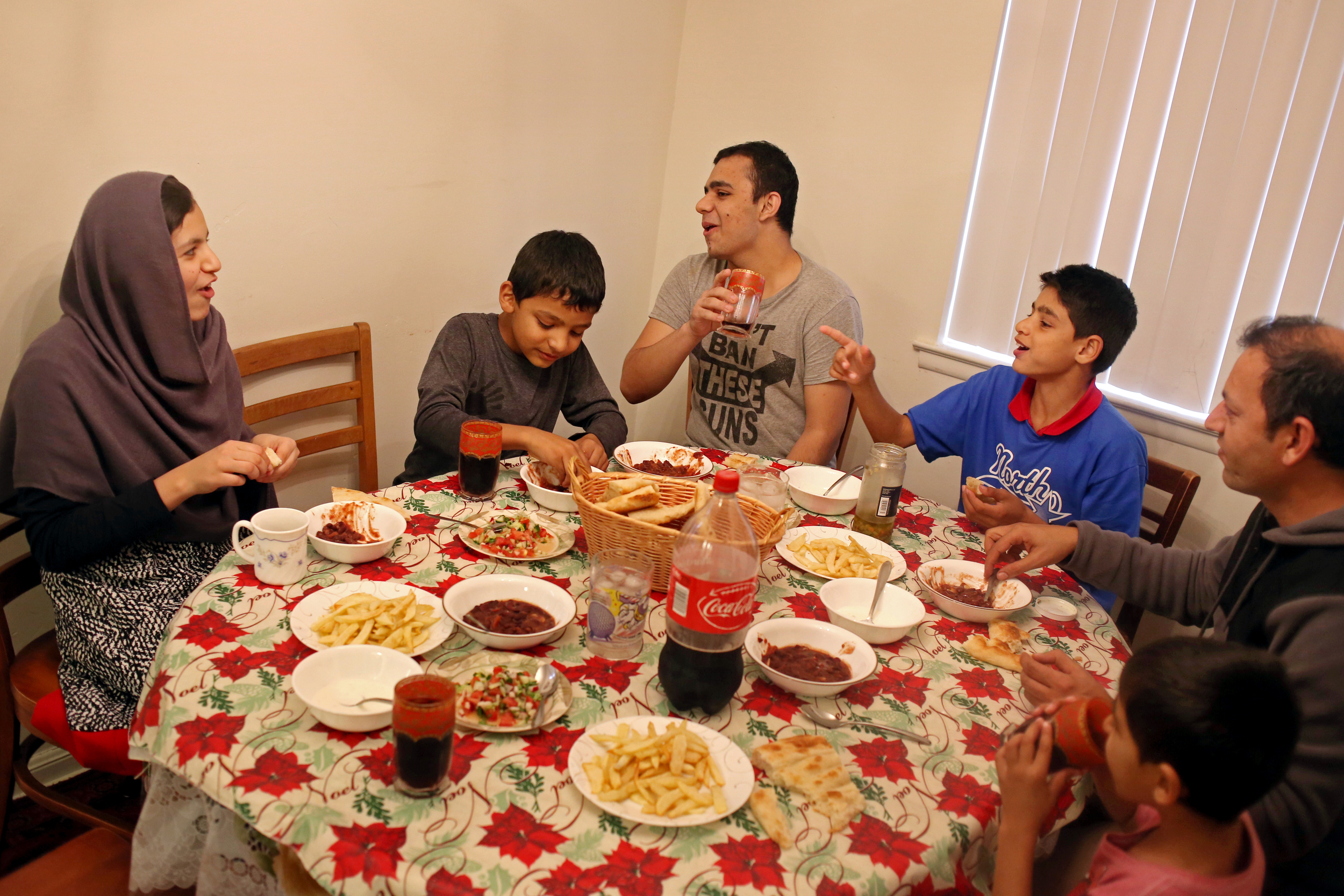 From left to right, Khatera, 13, Kawoon, 8, Basir, 17, Janan, 11, Ezatullah, 38, and Ehsanullah, 6, eat dinner together at their home in Lansing, Mich. The family uses dinner time as a way to catch each other up on the days events at school.