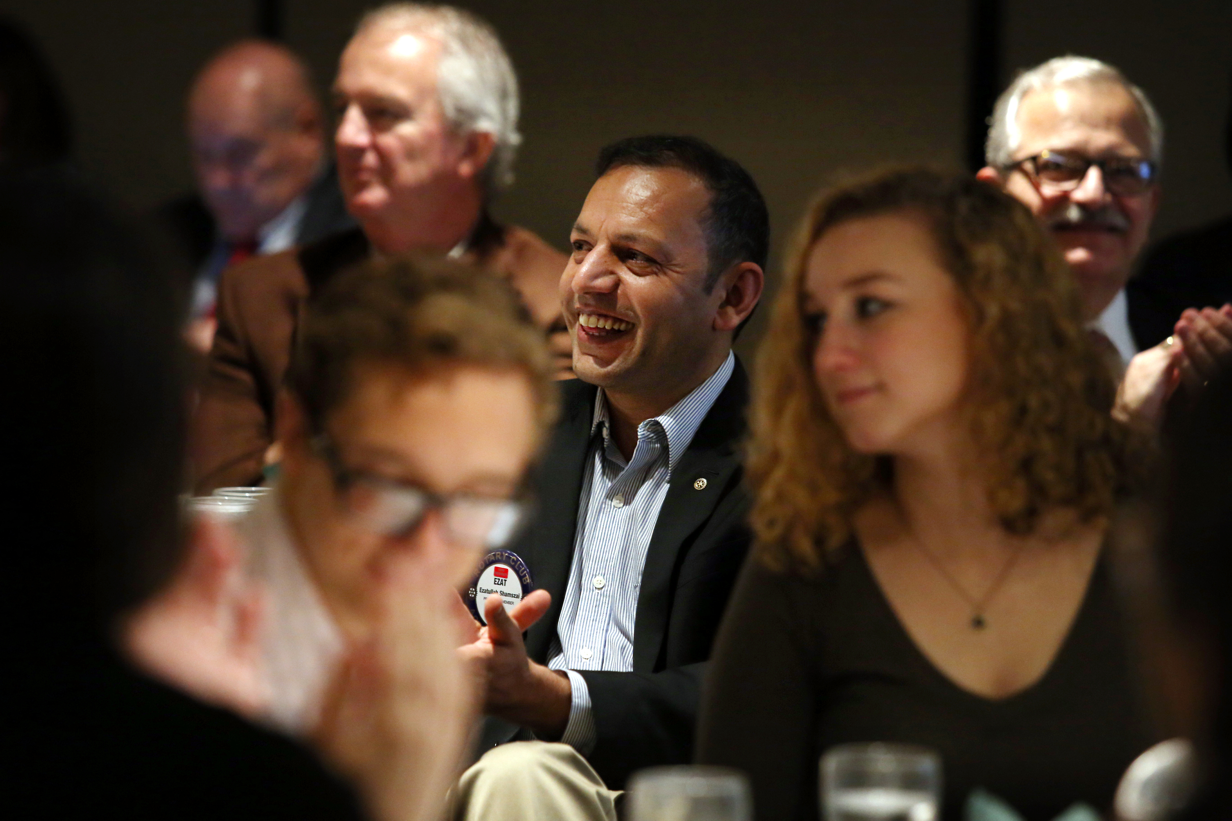 """Ezatullah listens to a speaker at the Rotary Club of Lansing. Ezatullah wants to stay involved in the community so he can meet more people. """"I'm trying a lot to talk to people…to know more about the culture…I like to be engaged with the community. Being social just opens the door for you,"""" said Ezatullah."""