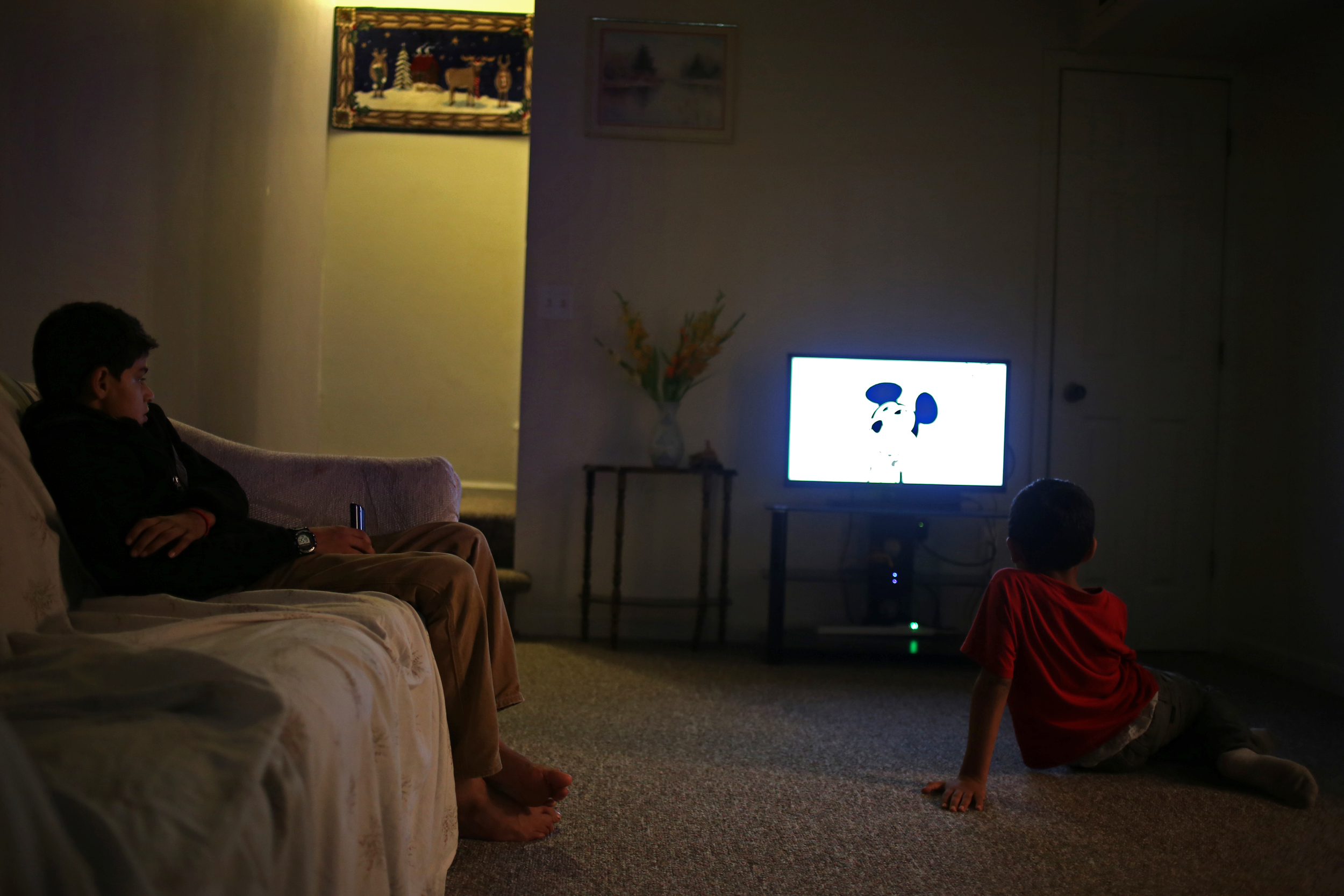 "Janan, left, and Kawoon watch television in the living room of their apartment. Their father, Ezatullah, worries that his children are becoming westernized and losing parts of their Afghan culture. ""We used to eat on the floor when we came here but the kids don't like doing that anymore,"" said Ezatullah."