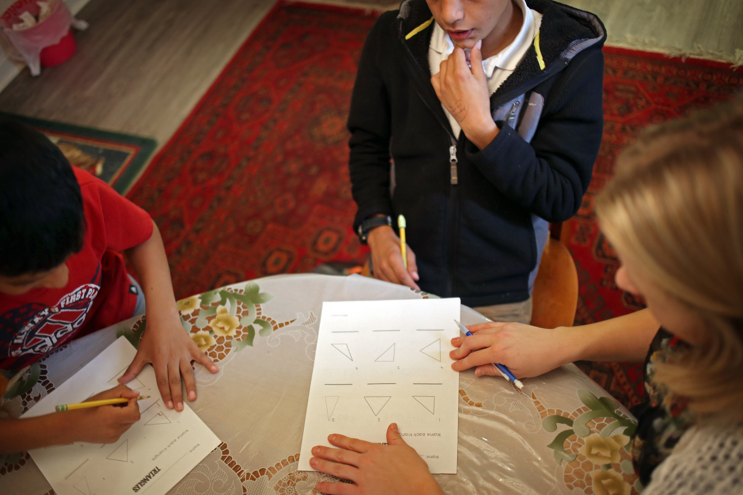 "Kawoon, left, and Janan get tutored by Central Michigan University student, Katilee Bensley at their home in Lansing, Mich. Bensley met the boys over the summer and continues to tutor them. ""When I tutored Janan at the summer reading clinic his independent reading level increased from a 6th grade level to an 8th grade level…Janan has a drive to do well in school and has told me his dream is to be a doctor one day."" said Bensley. Bensley also tutors Khatera and her younger brothers. ""When I started tutoring them in Lansing it started with just tutoring Janan. Then Khatera joined in, eventually I had all the kids around the table wanting me to teach them…It makes me so happy to see how much love and passion they have to learn,"" said Bensley."