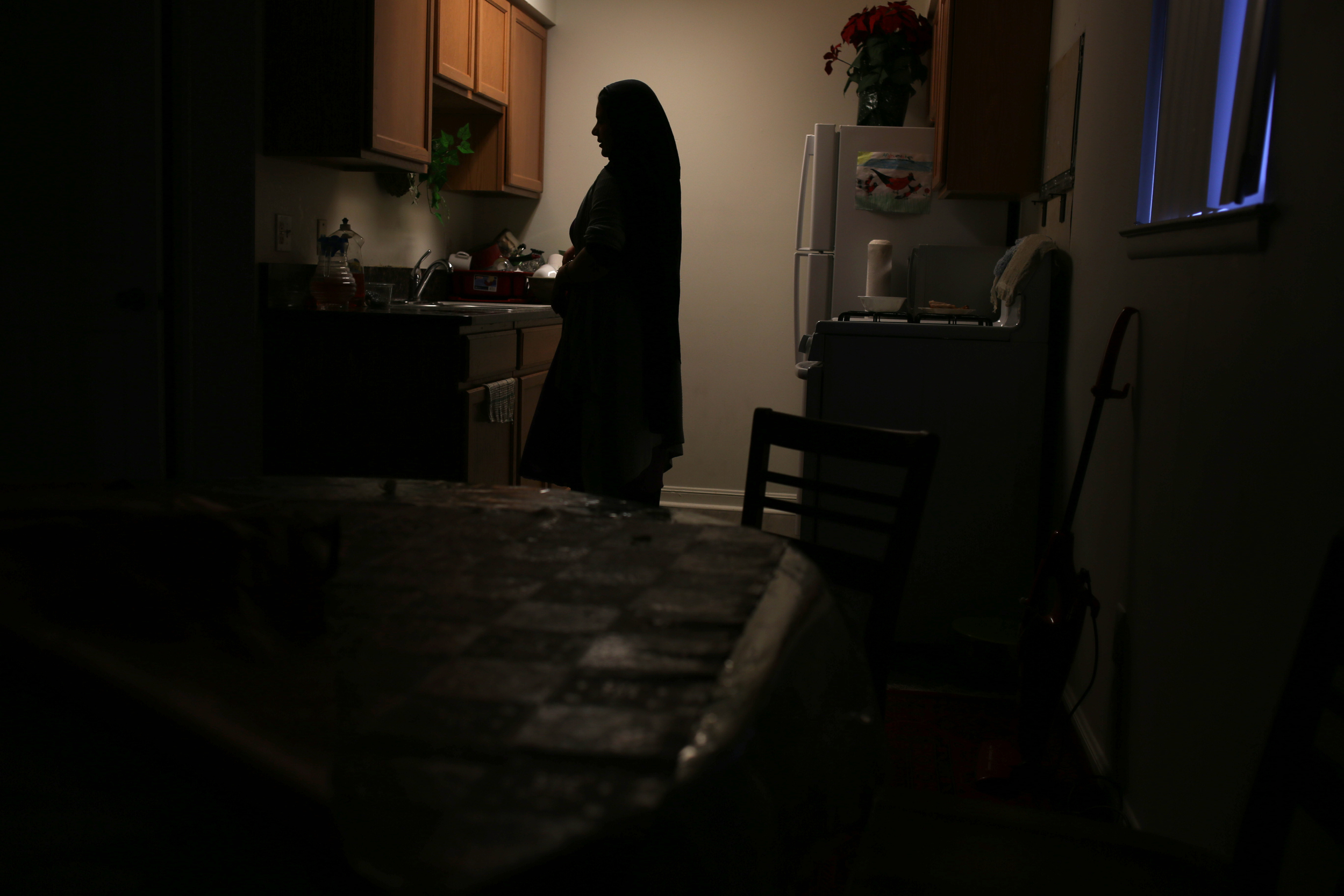 Pashtoon cleans the kitchen within her apartment. Pashtoon struggled both physically and emotionally when they moved to the United States but is much happier now. She takes English classes four times a week and is getting help from her children and husband.