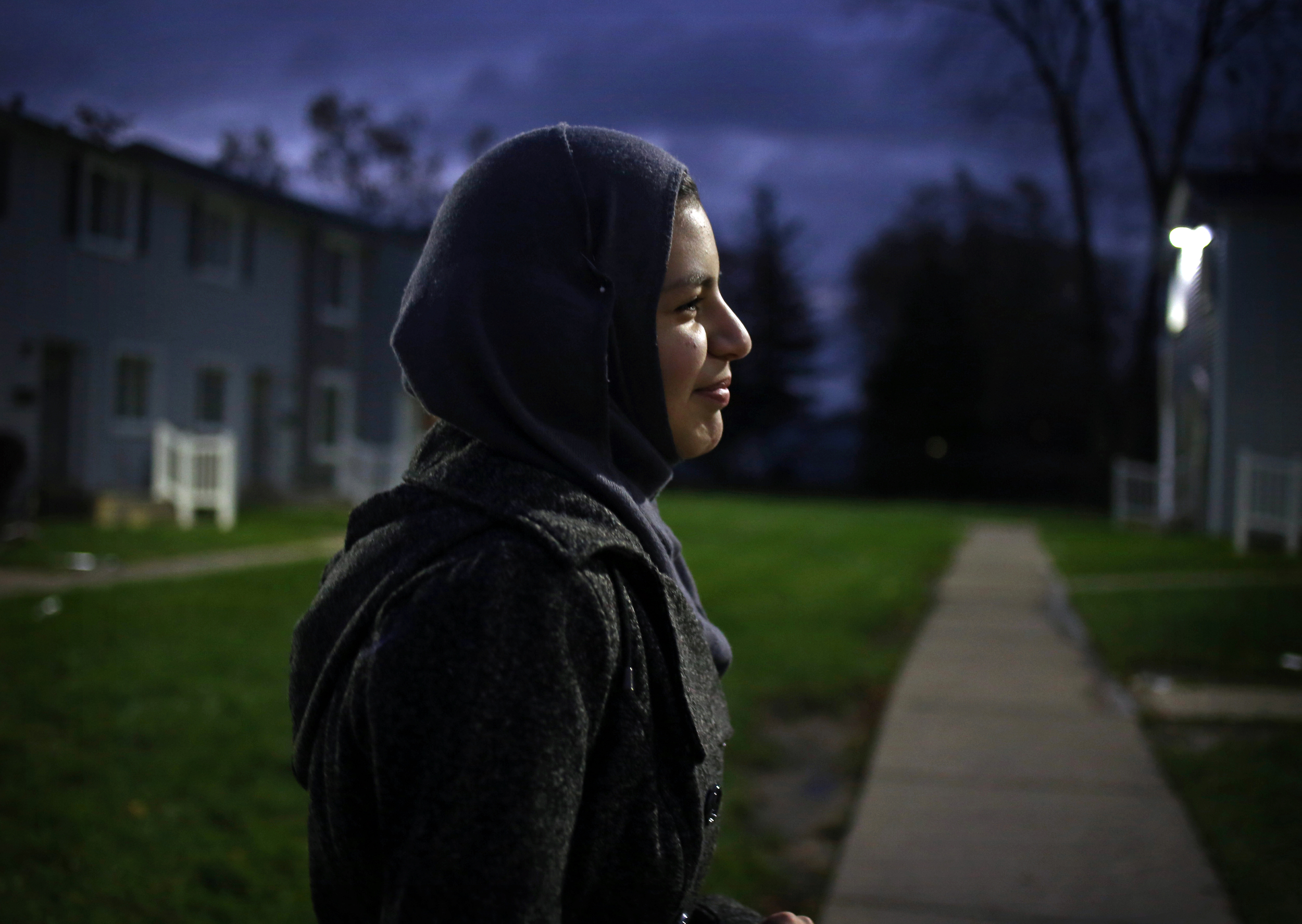 """Khatera walks to the bus stop on her way to school. As an 8-year-old in Afghanistan, Khatera had difficulty passing the third grade because of the education system. When they moved to Michigan, she was placed in sixth grade and is excelling in her education. """"It was the education system, they didn't know how to handle her,"""" said Ezatullah. """"I want to be a teacher,"""" said Khatera."""
