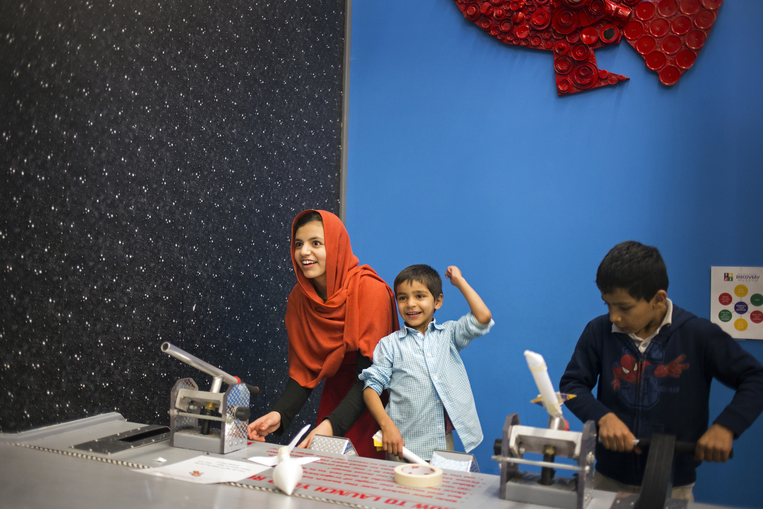 Khatera, Ehsanullah, and Kawoon launch paper rockets at the Mount Pleasant Discovery Museum. Their grandmother, Eileen Jennings, plans activities for the kids when they visit her in Mount Pleasant. Jennings helped Ezatullah and his family when they first moved to Lansing, taking them to get groceries weekly and opening up her home to them when they needed it.