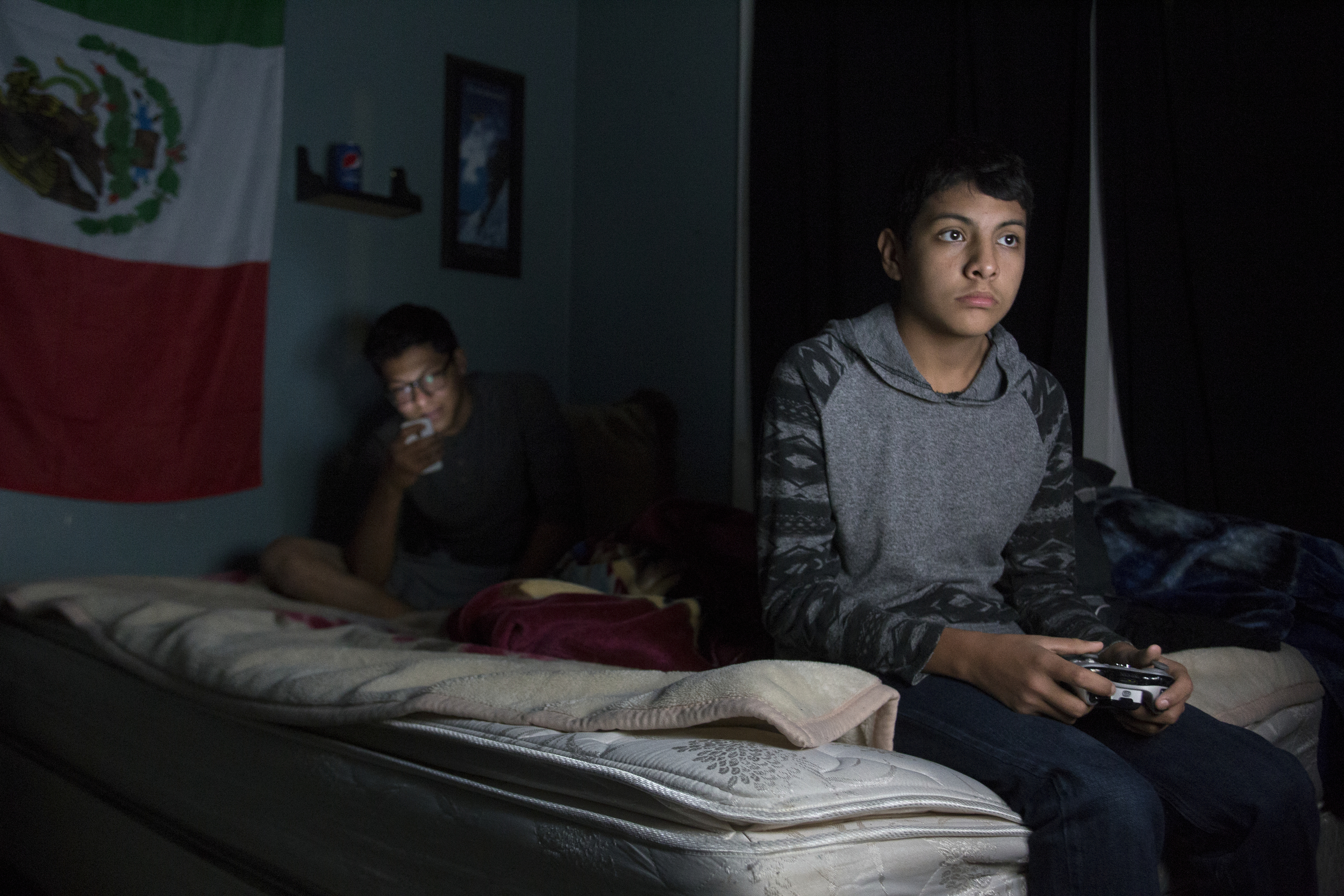 Ignacio Jurado, 17, left, and his brother Leo, 13, right, play video games and share YouTube videos with each other in the camps at Uncle John's Cider Mill. The brothers have a very close relationship and spend a lot of time together.
