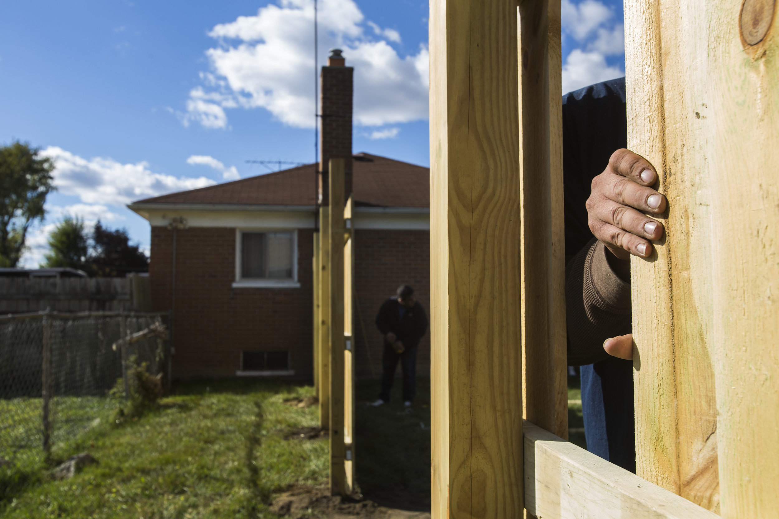 Edwin Silva, center, adjusts a power tool while working with his father Roberto and co-worker Victor Hernandez, right, as they install a custom-built wood fence for a homeowner in Inkster on a Sunday afternoon.
