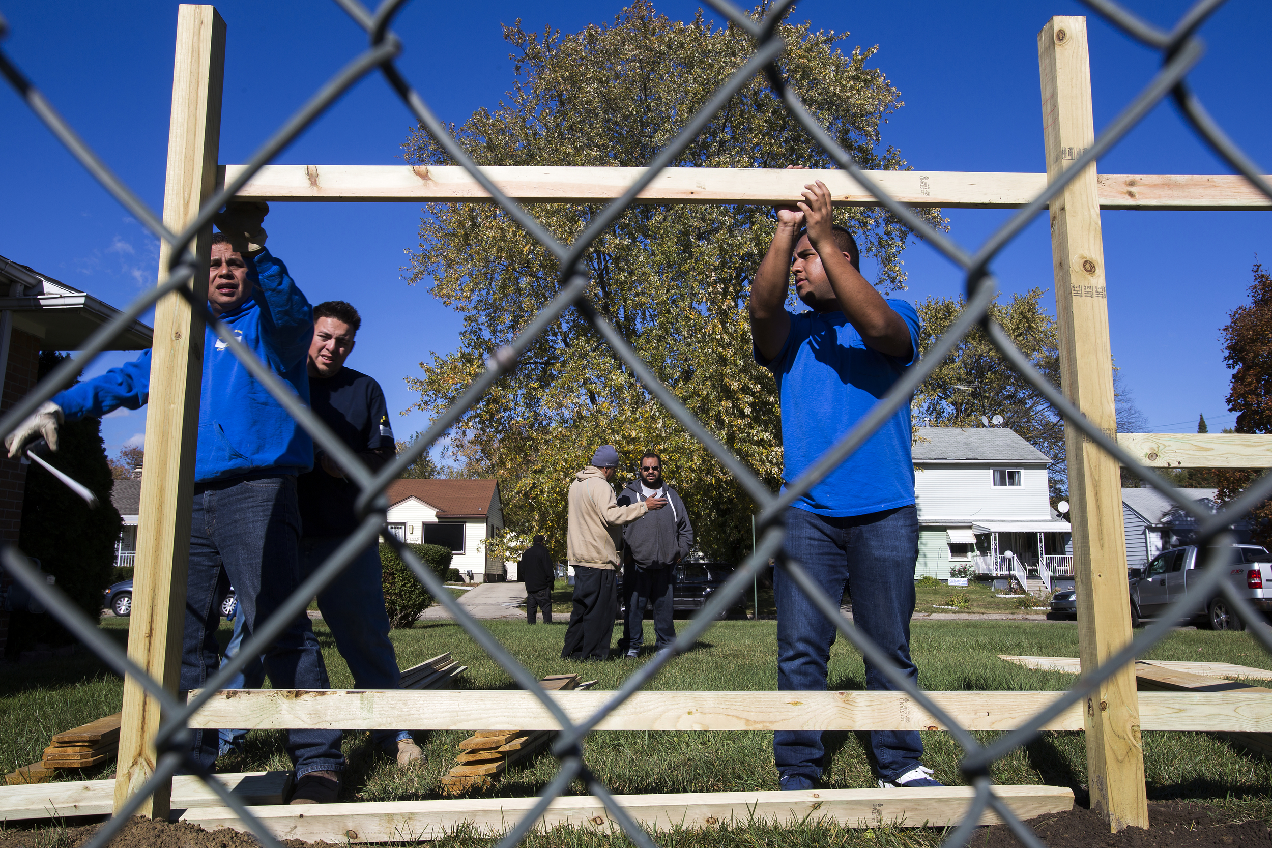 An older metal chain-link fence is replaced by a custom-built wood fence as Edwin Silva, right, his father Roberto, left, and co-worker Victor Hernandez work together on the installation for a homeowner in Inkster.