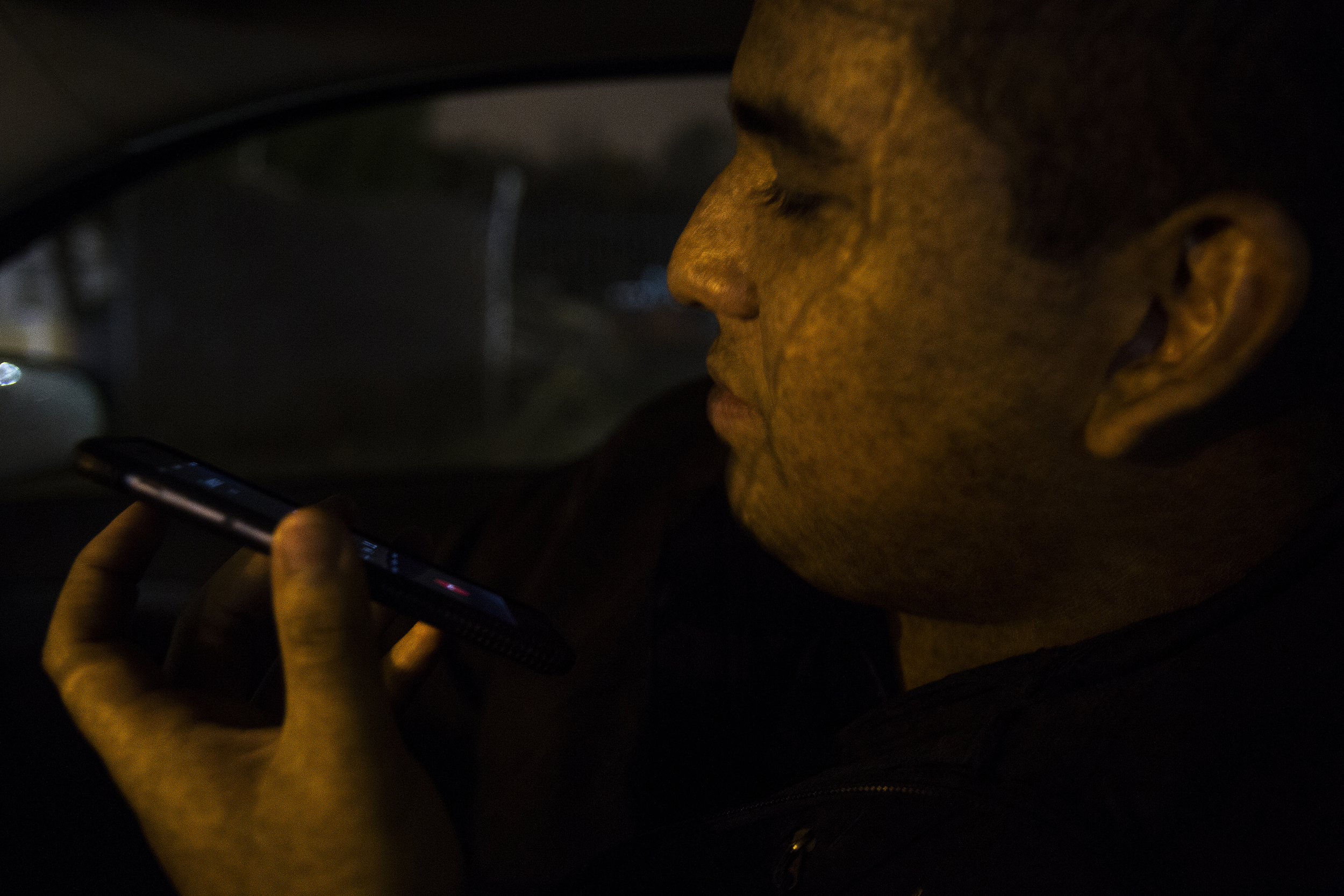 Rain falls on the car window while Edwin Silva speaks with a friend in the passenger seat parked in front of his Westland home.  Without a legal immigration or citizenship status, Silva is unable to obtain a valid driver's license from the state of Michigan.