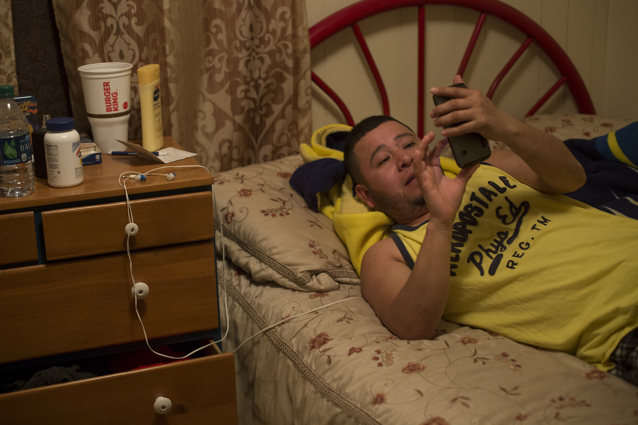 """Alberto, lays in bed looking at Facebook on his phone. He was a police officer in Salina Cruz, Mexico. He came to America with his two sisters by bus for $2,000 each. He lived in North Carolina working multiple jobs before he left on his own to work on the dairy farm. """"Every night I cry, I miss my family, here I have no sisters, parents or friends, so I drink beer every night to fall asleep,"""" said Alberto while looking at a photo of a Christmas tree from the year prior."""