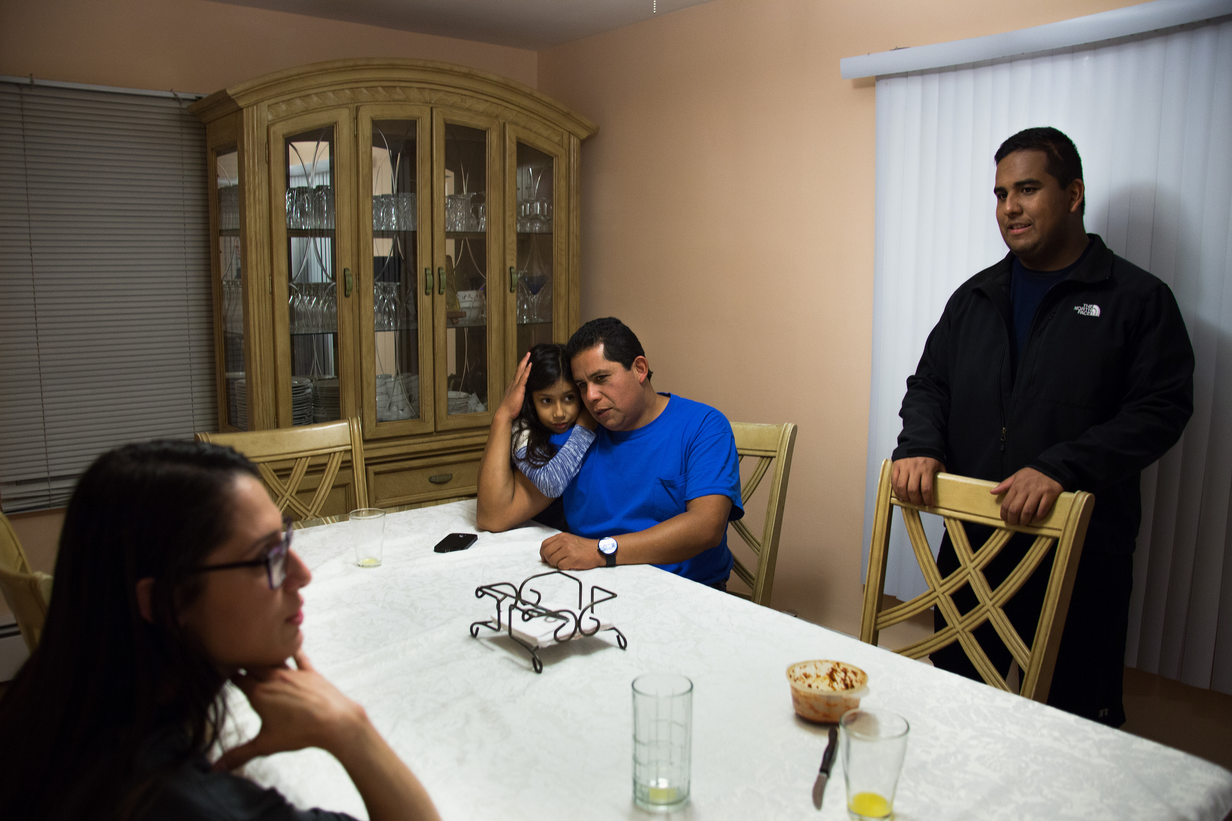Roberto Silva, center, embraces his daughter Elizabeth, 11, as the family including Edwin Silva, 22, right, his mother Aida, not pictured, and Adrianna Beltran, 21, left, a family friend, come together around the dinner table to converse about their day.