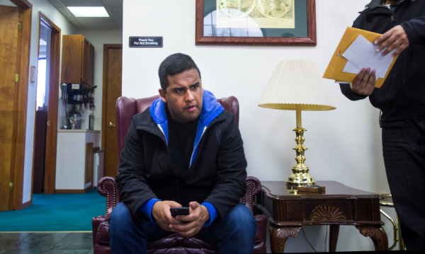 For the fourth time in two months, Edwin Silva waits in the lobby to finalize an I-589 application, withholding of removal, with his immigration lawyer's assistant at the main office in Dearborn. Photo by Andraya Croft
