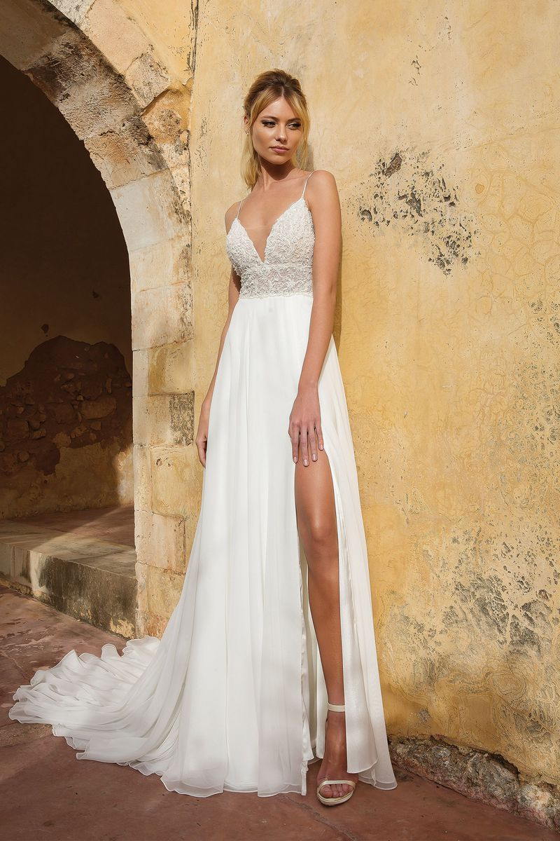 Style: 88035   Movement is limitless in this flowy A-line gown featuring beaded spaghetti straps. Hand beaded appliques adorn the illusion bodice that then leads to a clean tulle skirt with a slit.