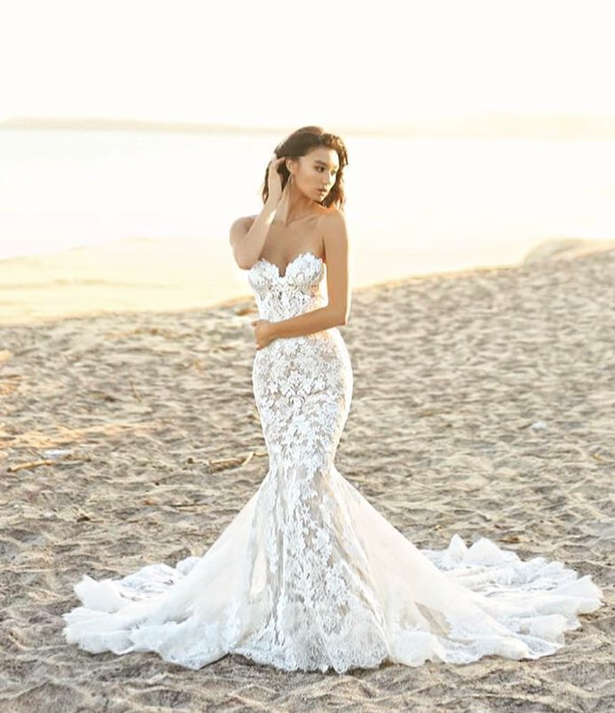 NOLEN  The perfect lacy mermaid gown. This full-length dress gorgeously fuses embroidered lace, corded lace and Chantilly lace to create a stunning vision from the unlined, strapless sweetheart neckline bodice all the way down to the showstopping illusion lace train with a scalloped hem.