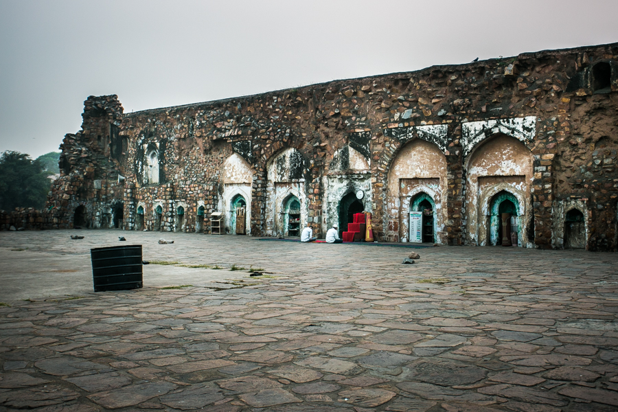 Two men paying homage to the Jinn in the ruins of the Feroze Shah Kotla Fort.