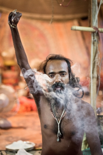 """This sadhu, imbibing a joint,says he has kept his hand raised for six years. You can observe that his raised hand is deformed. Sadhus take on such ascetic assignments,  which fall  under the yogic practice of   pratyahara  o  r   """"sensory withdrawal,"""" to prove their devotion."""