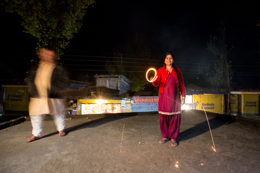 """Arun's mother, Miri, lighting a sparkler on the """"patio"""" (really the roof of another store) in front of the Herr's shop."""