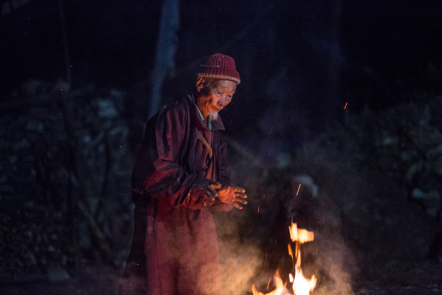 A villager keeps warm by a fire in the village of Namrung located in the Manaslu reserve.