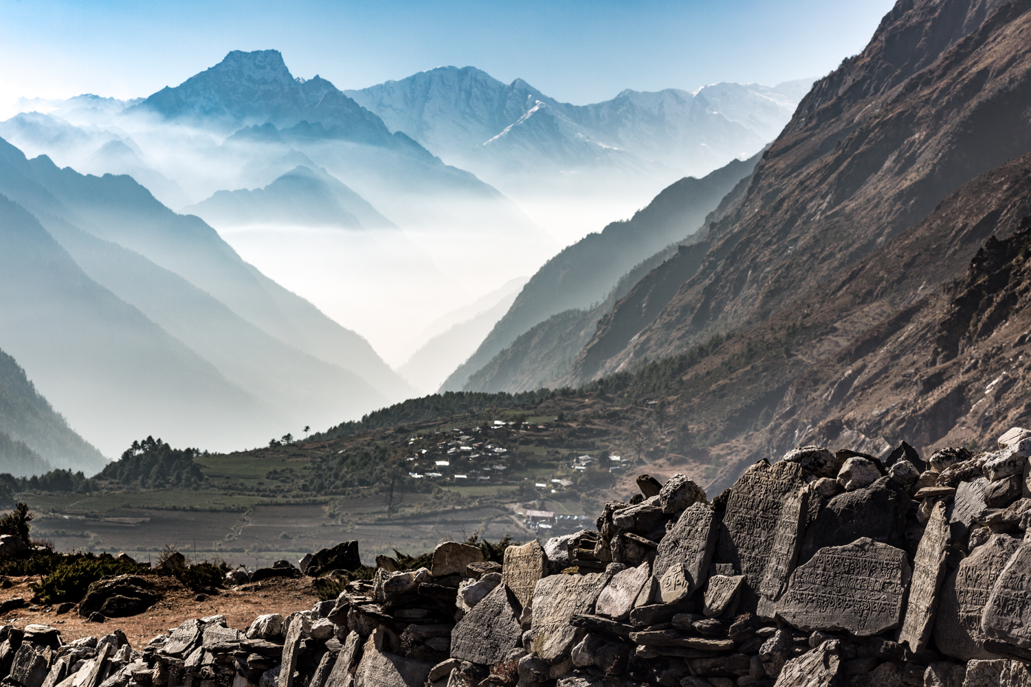 Tsum Valley. In the foreground are mani stones bearing Budhist mantras in memory of deceased persons.