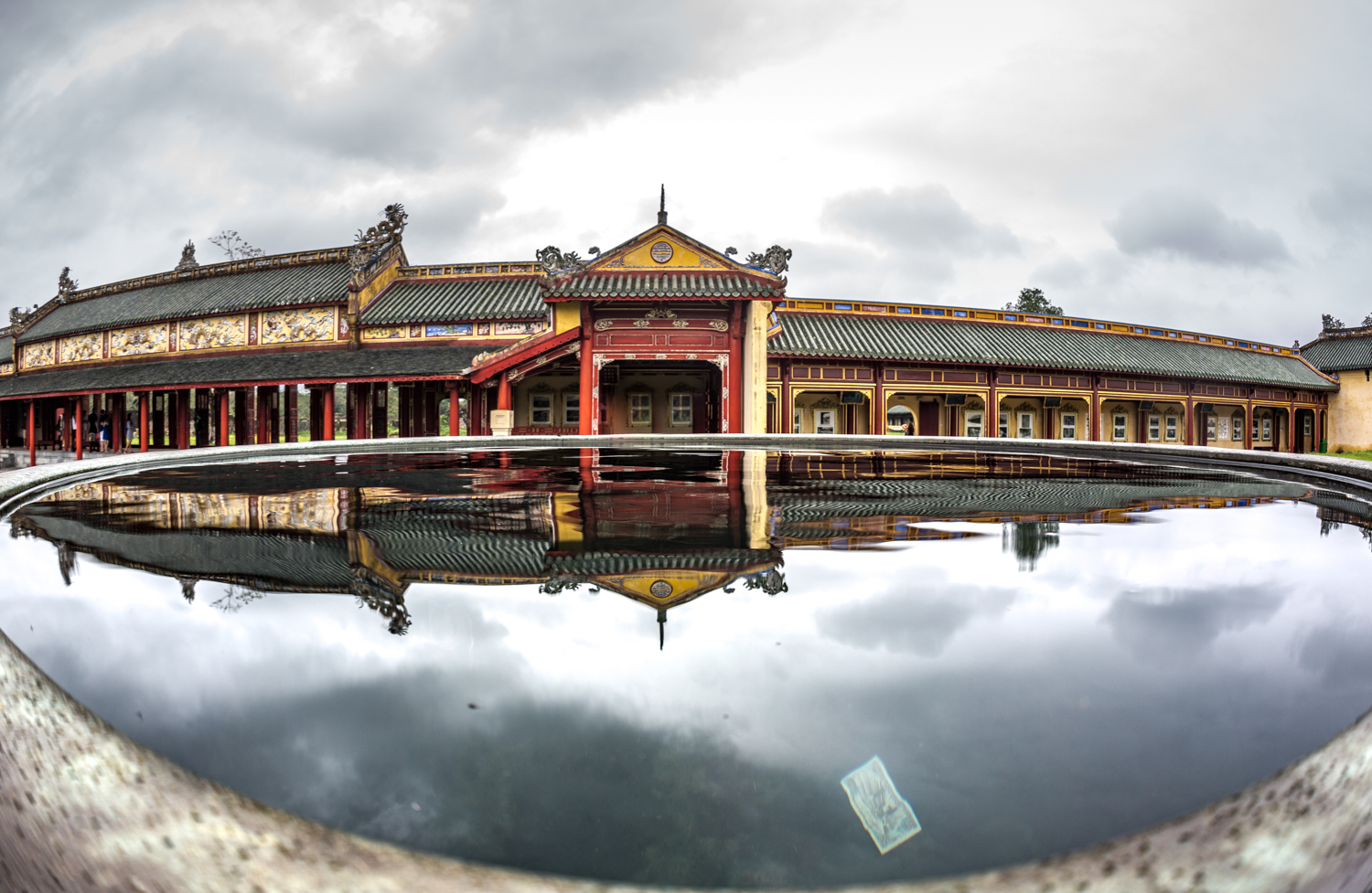 Imperial Citadel in Hue, the national capital from 1802-1945 under the Nguyen Dynasty. Sections of the citadel were damaged during the Vietnam war. Visitors deposit cash into the water basins for good luck.