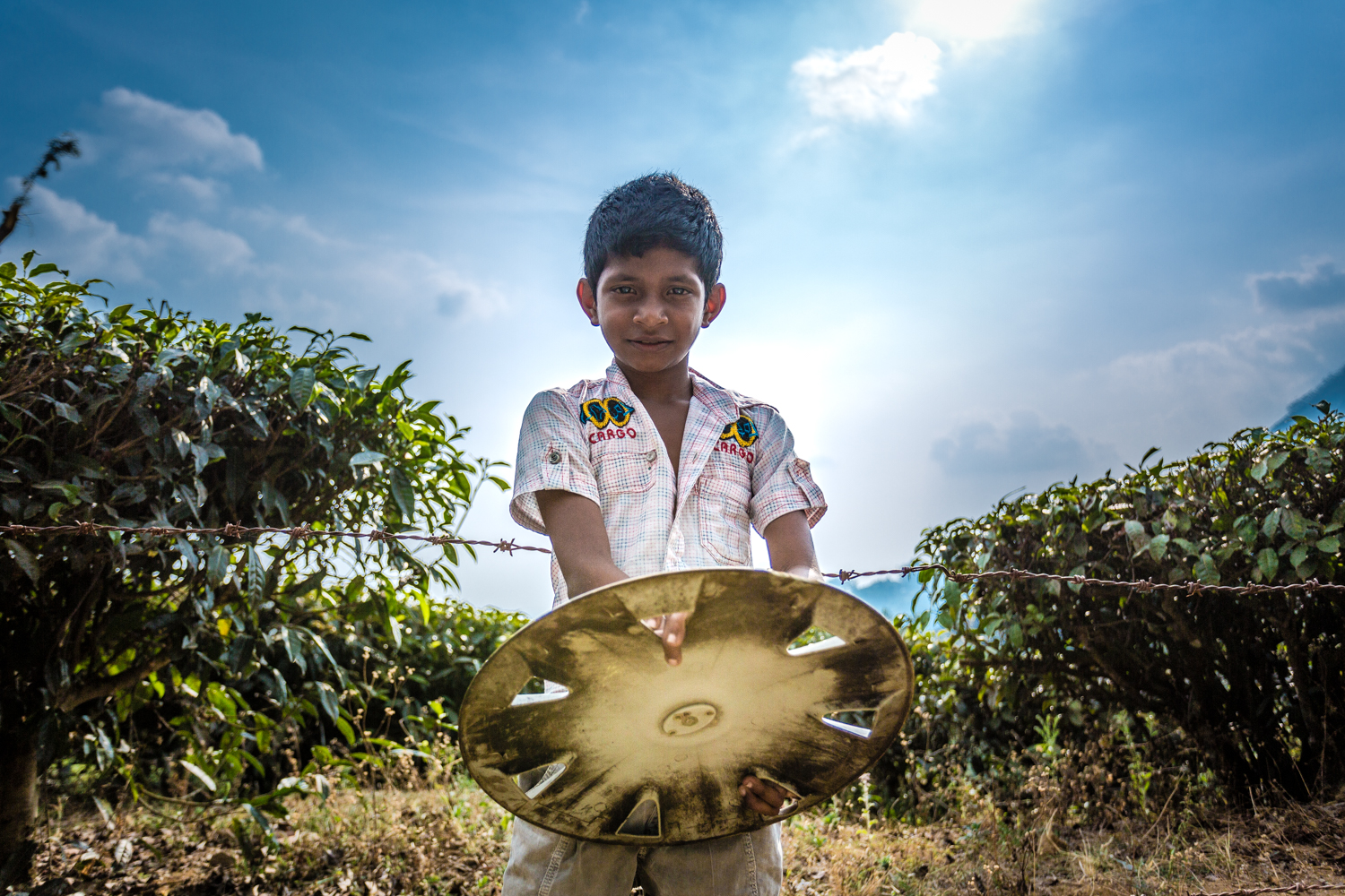 Villager playing with a hubcap near in a the plantation near Munnar, Kerala.