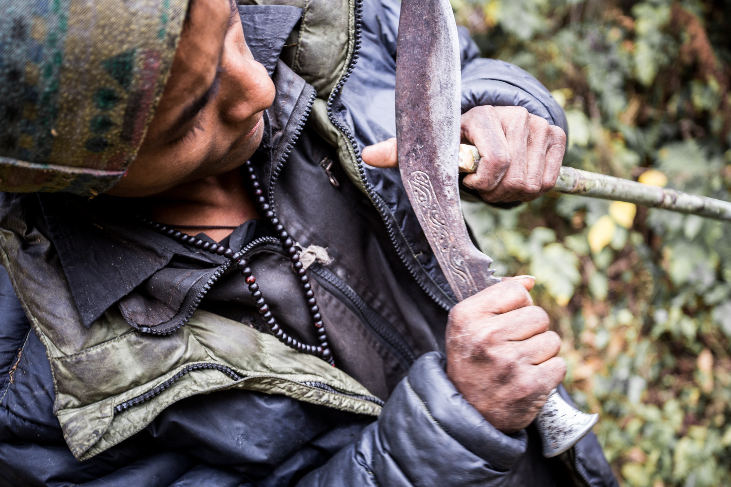 Villager in the Manaslu Reserve carving bamboo into a walking stick.