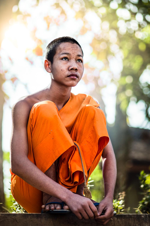 Young monk taking a break from gardening at Wat Mahathat in Luang Prabang.