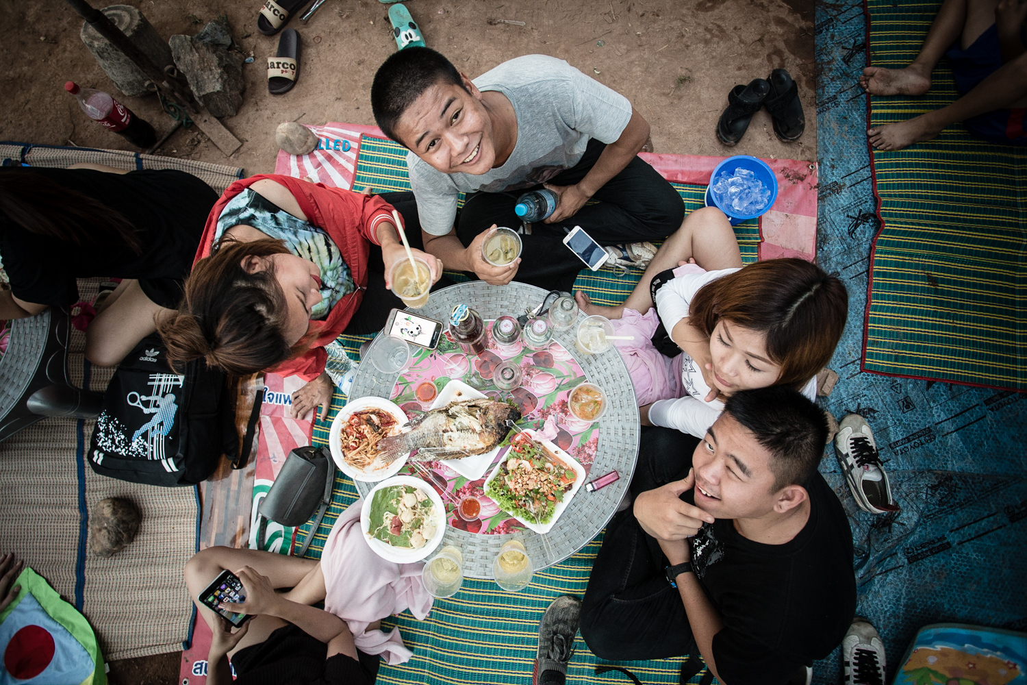 Young Thais hanging out on the banks of the Nan River, eating traditional foods and drinking watered-down whiskey.