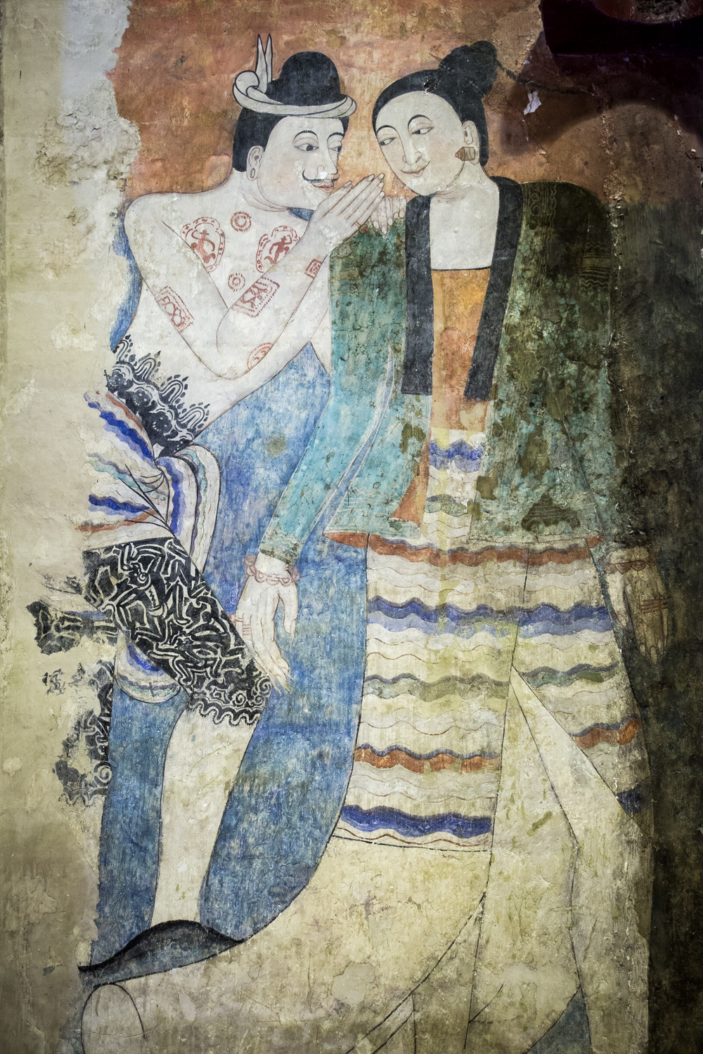 Thai Lü artist, Thit Buaphan, brazenly painted himself flirting with a women among his famed murals in Wat Phumin.