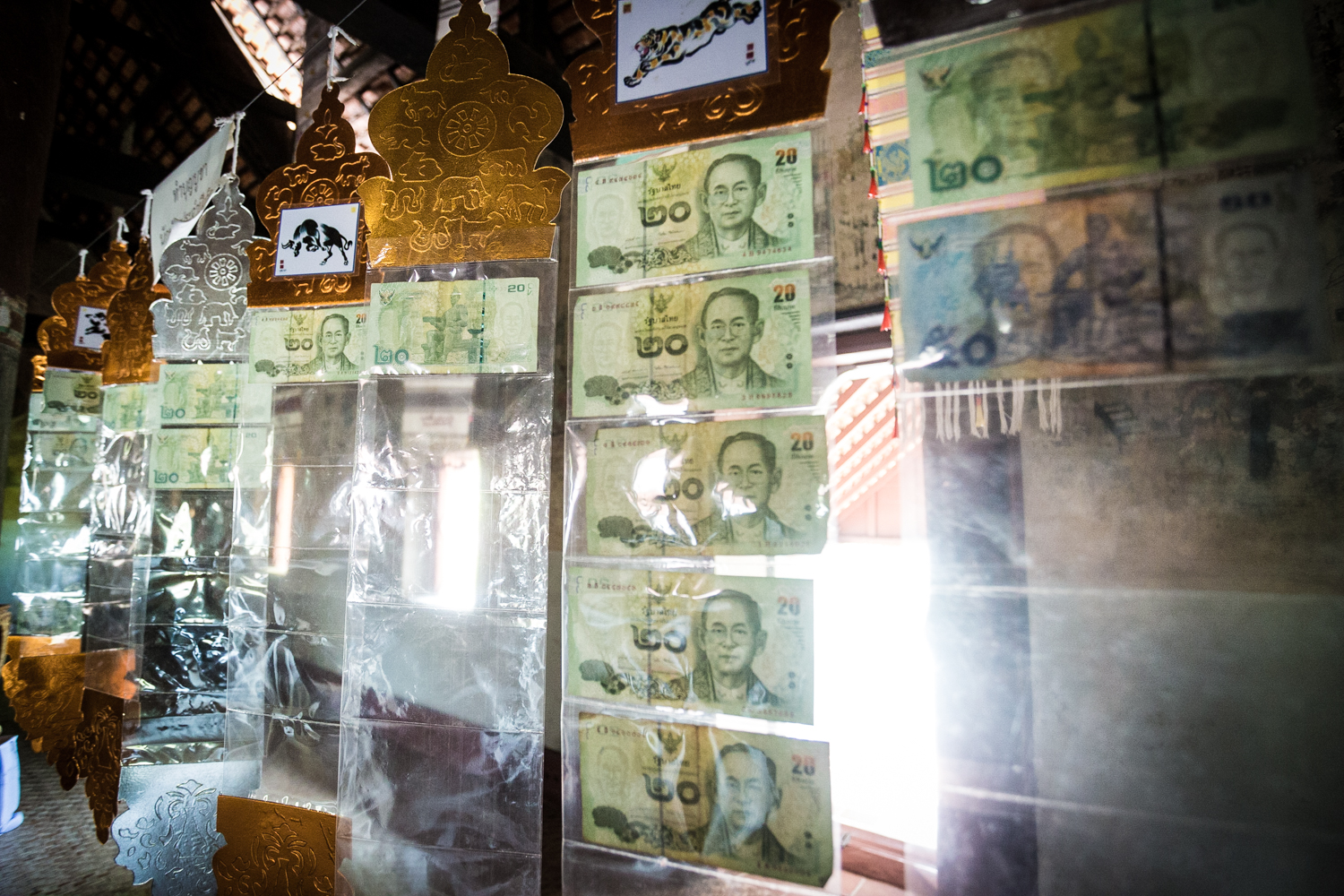 "Visitors to the Nong Bua Temple may donate ""lucky money"" by slipping a bill inside these hanging plastic sheets."