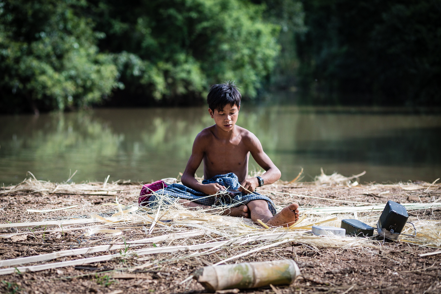 A boy preparing traditional baskets made from bamboo.