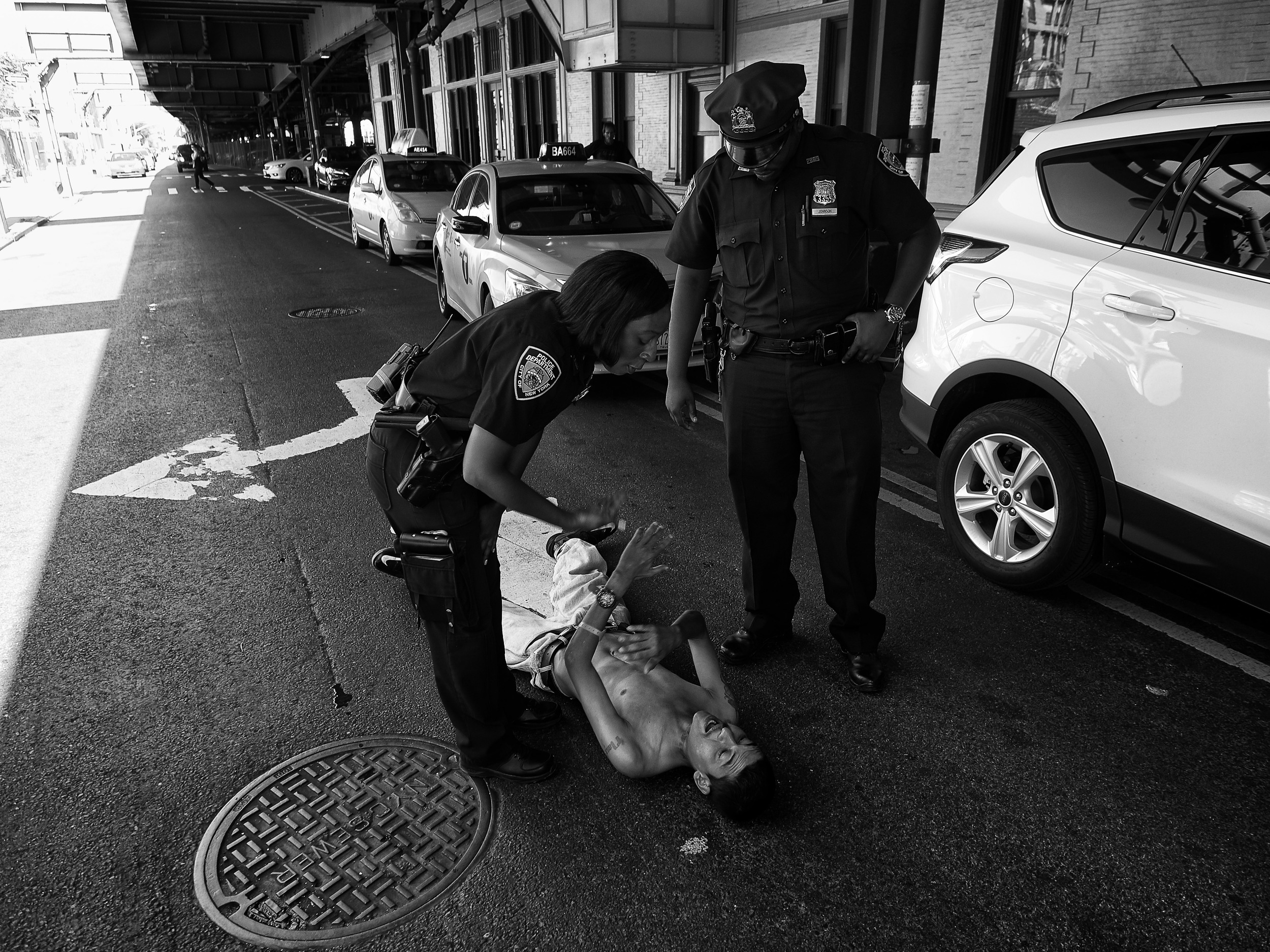 New York Police Department officers attempt to move an intoxicated, homeless man off the street on Thursday, September 17, 2015 in New York, N.Y.