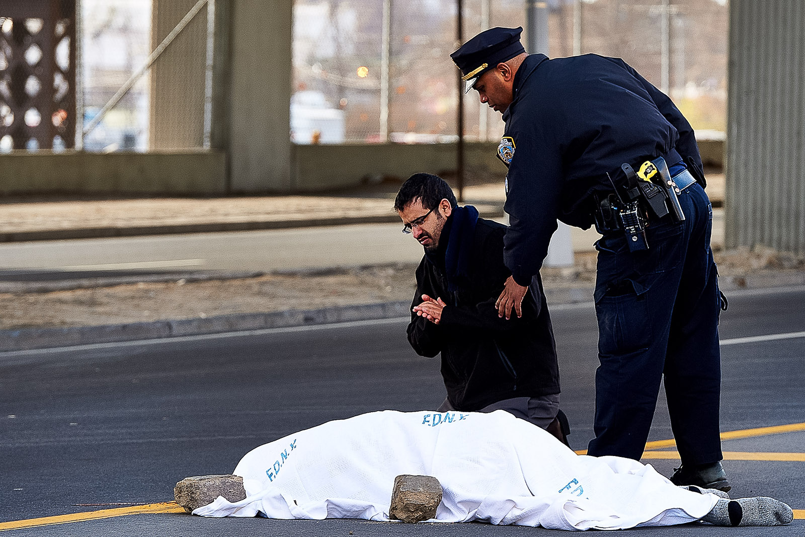 Waddah Mubarz kneels by the body of his cousin Abubakar Saleh by Austin Place on Bruckner Blvd. on Sunday, Nov. 24, 2013 in Bronx, N.Y. Saleh was struck by another vehicle as he examined his disabled vehicle on the upper level of the Bruckner Expressway.