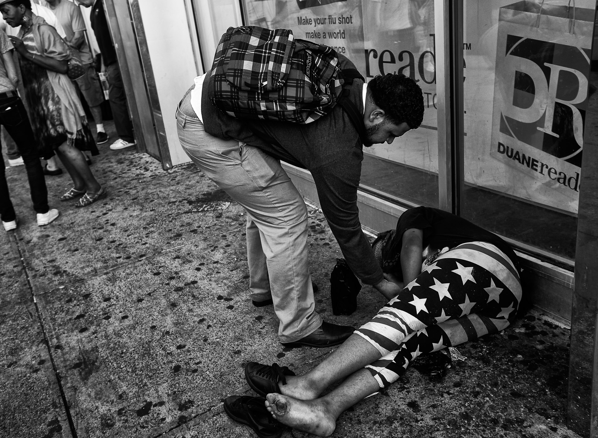A pedestrian checks the pulse of a woman who passed out on the street in an area of East Harlem that has experienced a surge in the use of synthetic marijuana, on Friday, September 18, 2015 in New York, N.Y.