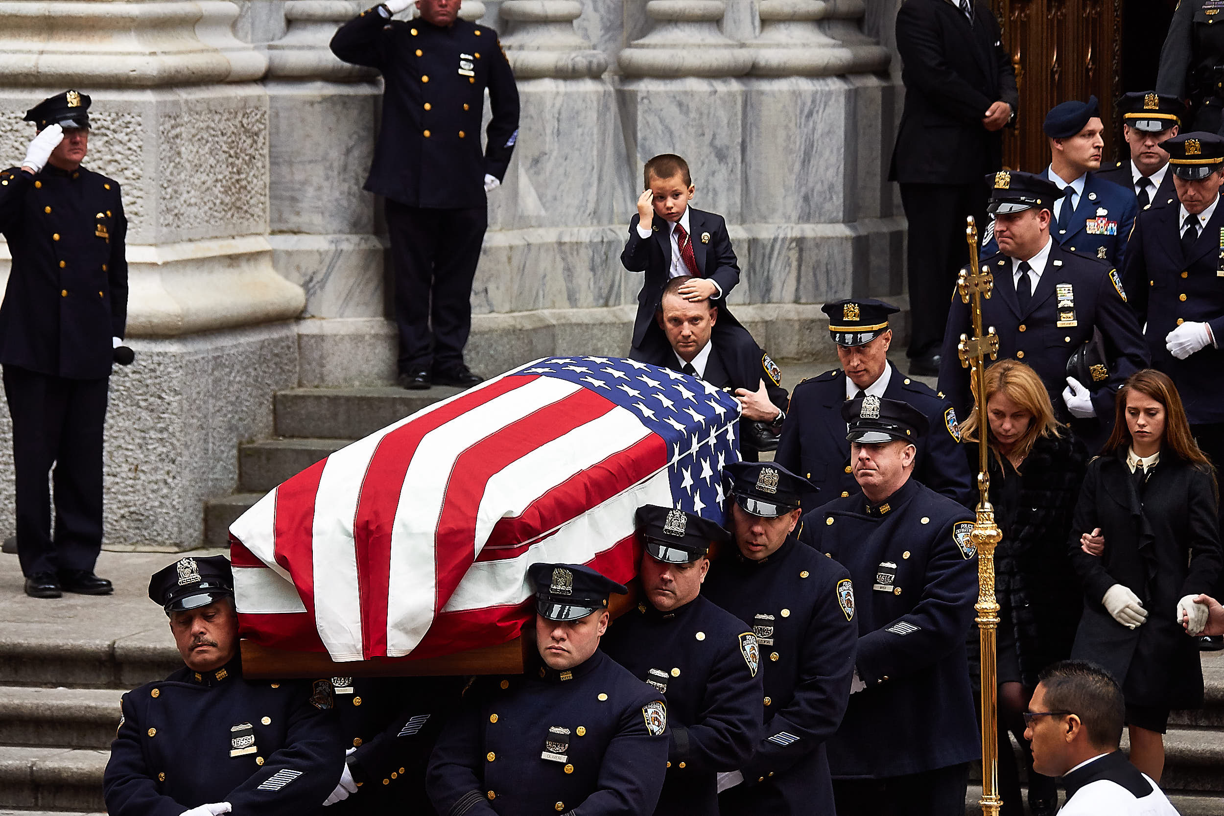 Detective Joseph Lemm's 4-year-old son, Ryan, center, salutes as pall bearers carry his father's casket out of St. Patrick's Cathedral following Lemm's funeral on Wednesday, December 30, 2015 in New York, N.Y.  Detective Lemm was killed along with five other soldiers by a suicide bomber in Afghanistan.