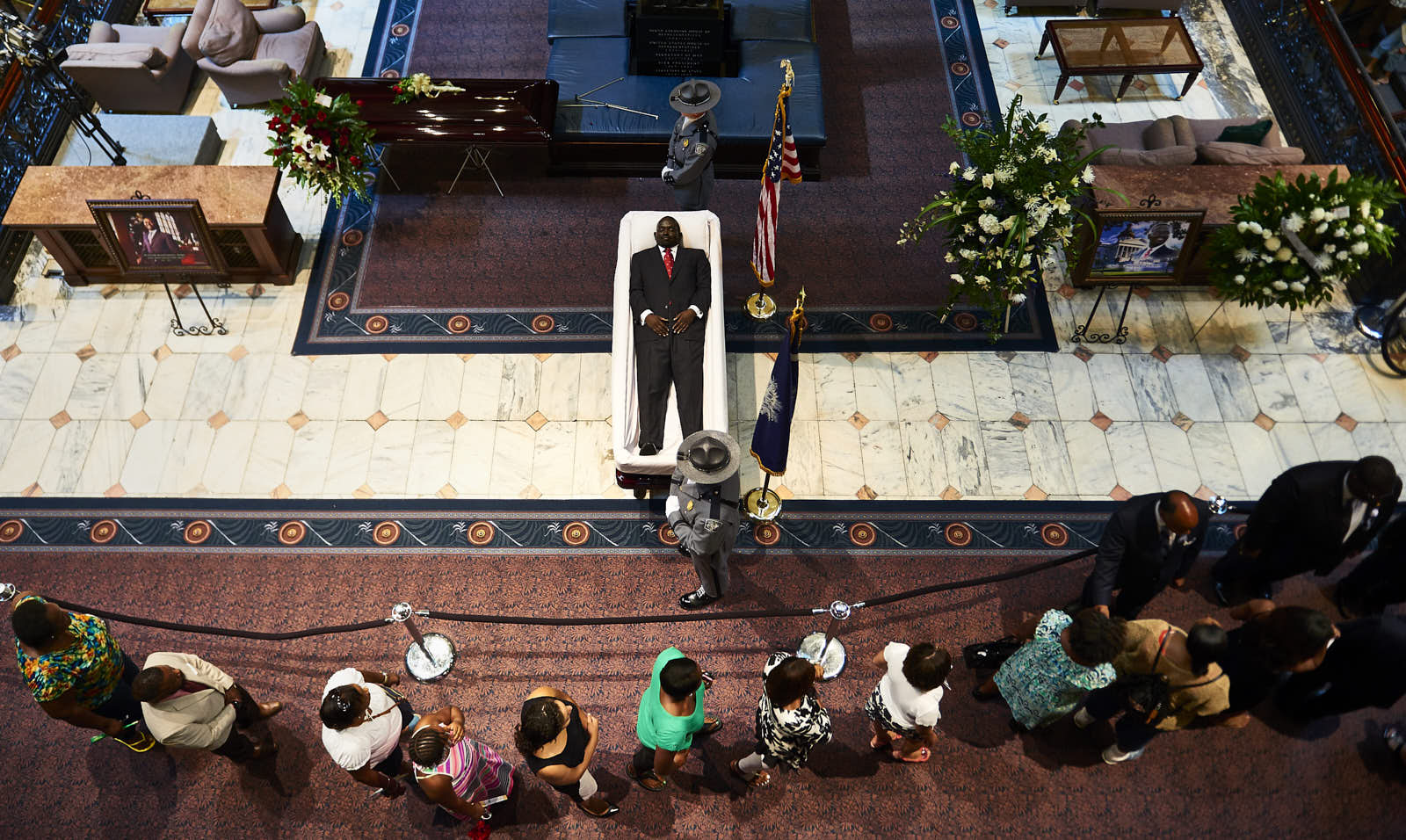 Visitors file past the coffin of Rev. Clementa Pinckney, as it lies in state inside the rotunda of the South Carolina Capitol building on Wednesday, June 24, 2015 in Columbia, S.C.  Pinckney, a state senator, and eight others were shot to death inside Mother Emanuel AME Church when gunman Dylann Roof opened fire during a Bible study session.