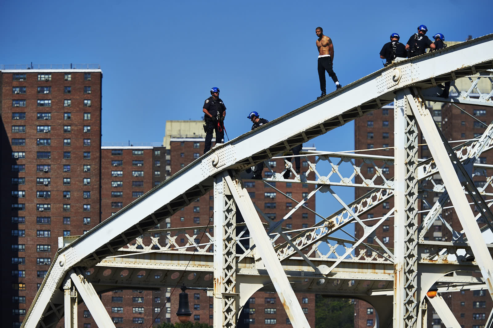 Police officers speak to a man who climbed the Macombs Dam Bridge on Wednesday, September 14, 2016 in the Bronx, N.Y.  The man was taken into custody and transported to a hospital for evaluation.