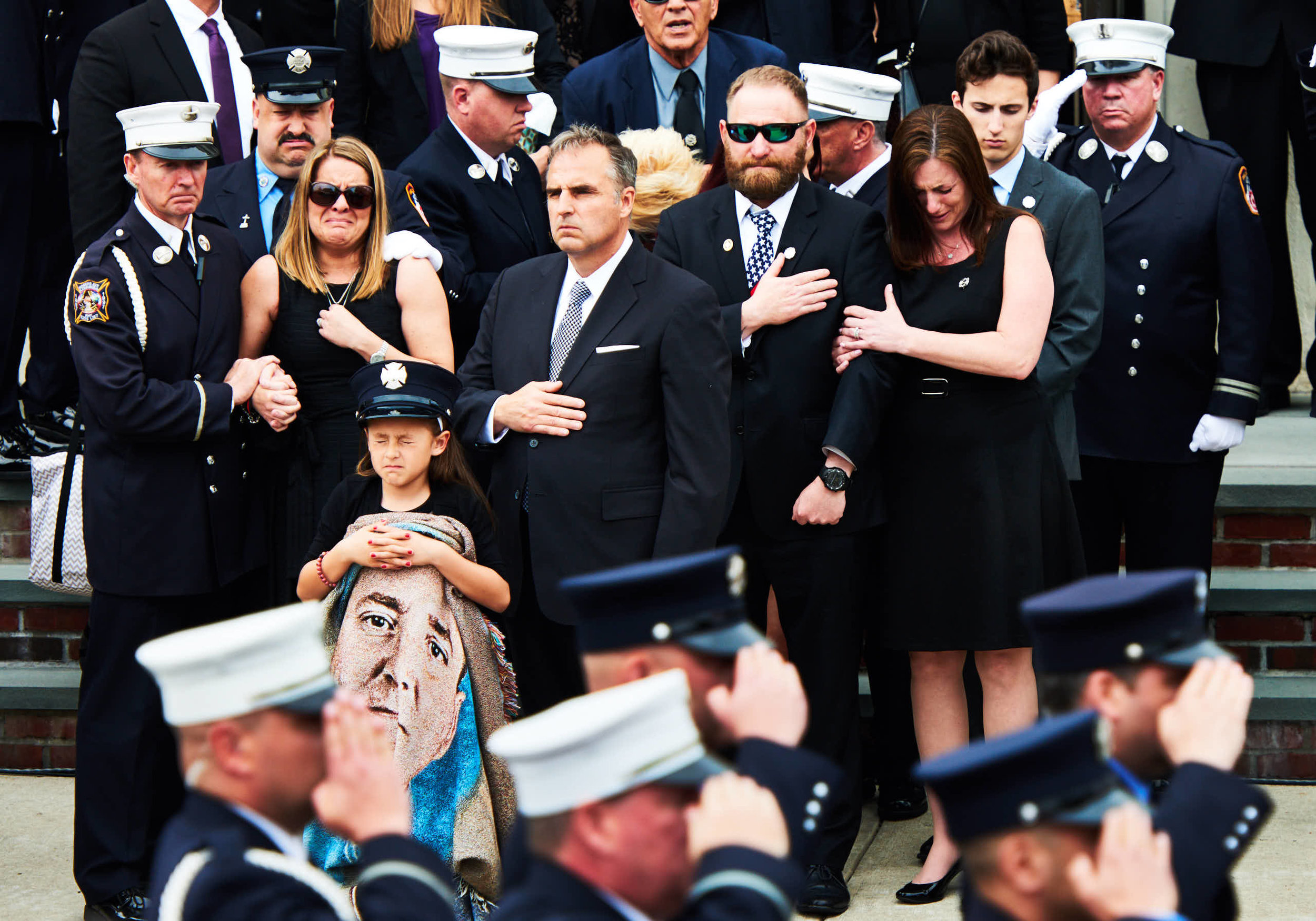 Marie Tolley, 2nd from left, the wife of fallen New York City firefighter William Tolley, and her daughter Isabella, 8, react as his casket is loaded onto a fire truck during his funeral on April 27, 2017 in Bethpage, N.Y. Tolley, a member of Ladder 135 Engine 286 in Glendale, and a Bethpage native, was killed while battling a blaze in Ridgewood, Queens, on April 20.